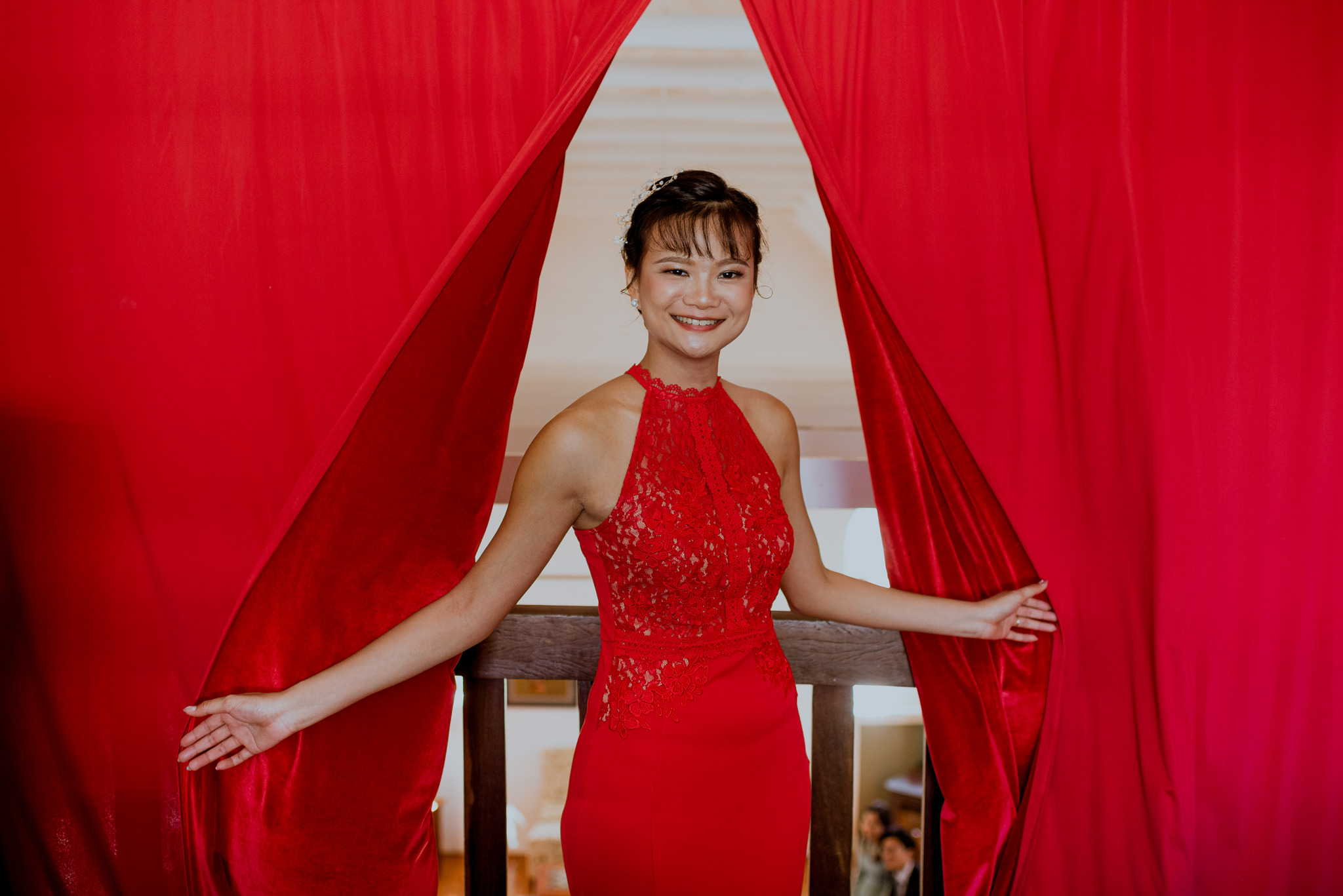 An asian woman in a red dress flings open a red curtain