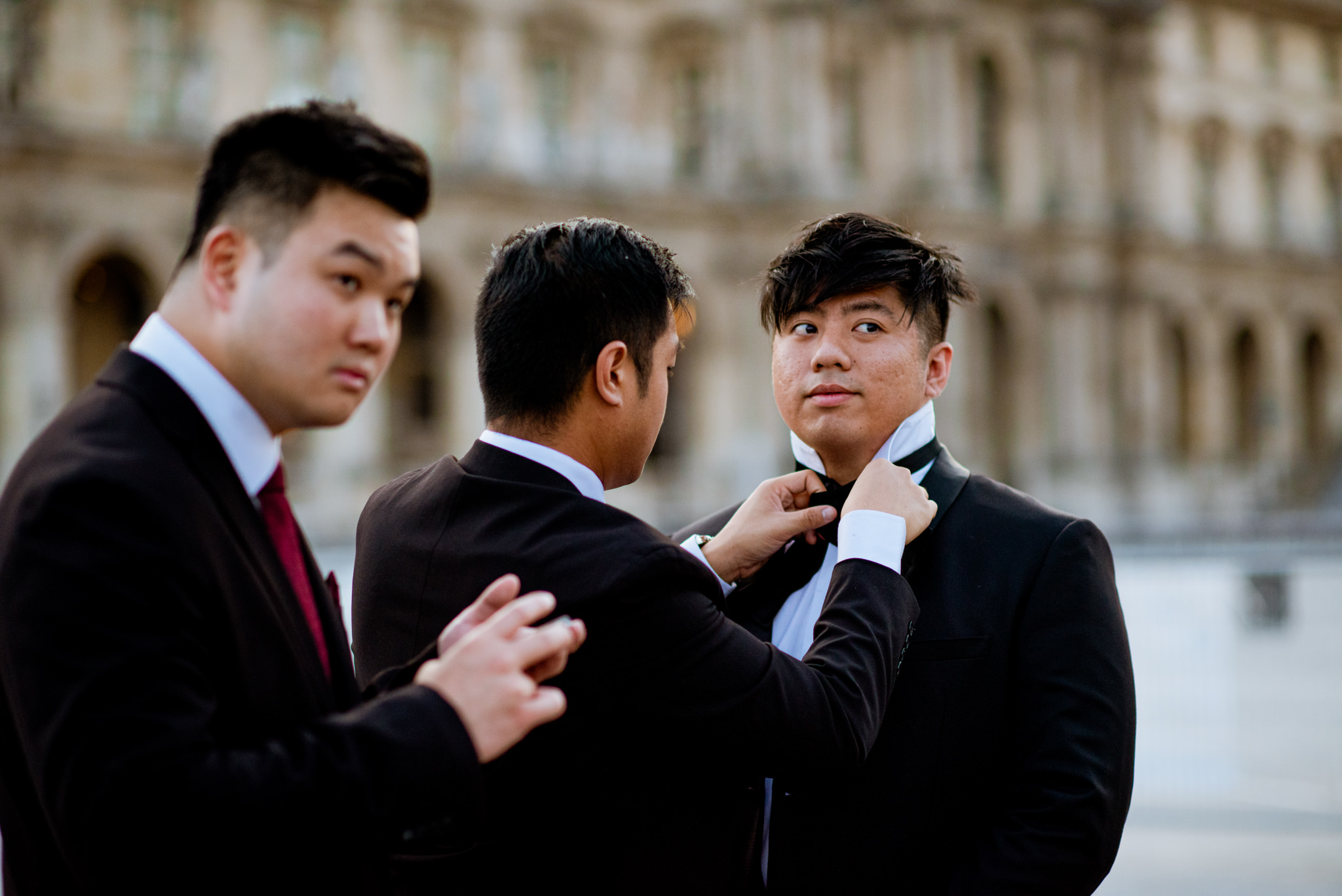 An asian man gets his bow-tie tied by his friend in front of the Louvre