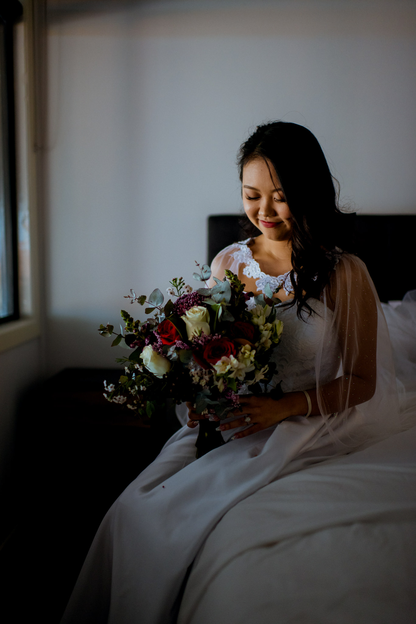 A bride gently smiles at her bouquet as she sits on a bed