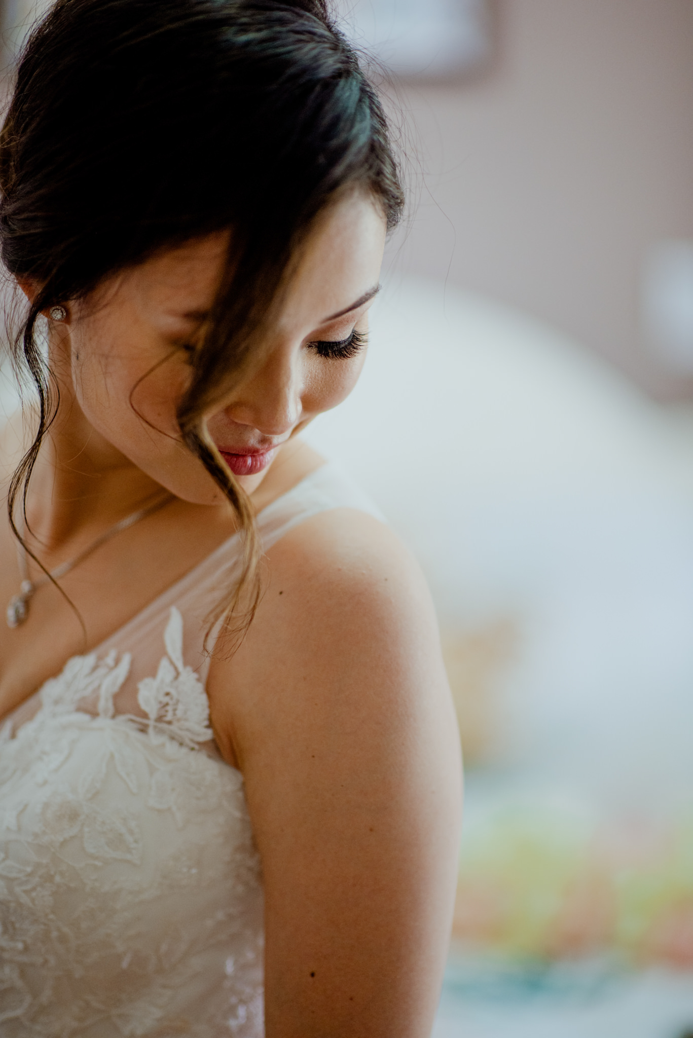 A bride gently looks down at her wedding dress and smiles