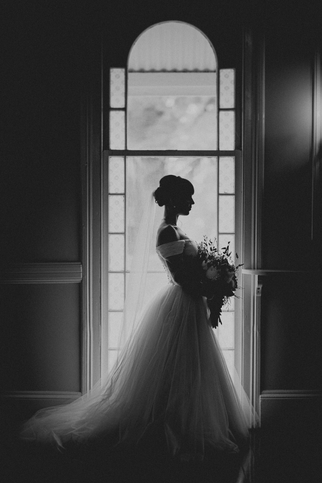 A silhouette of a bride in her wedding dress and bouquet in front of a large window