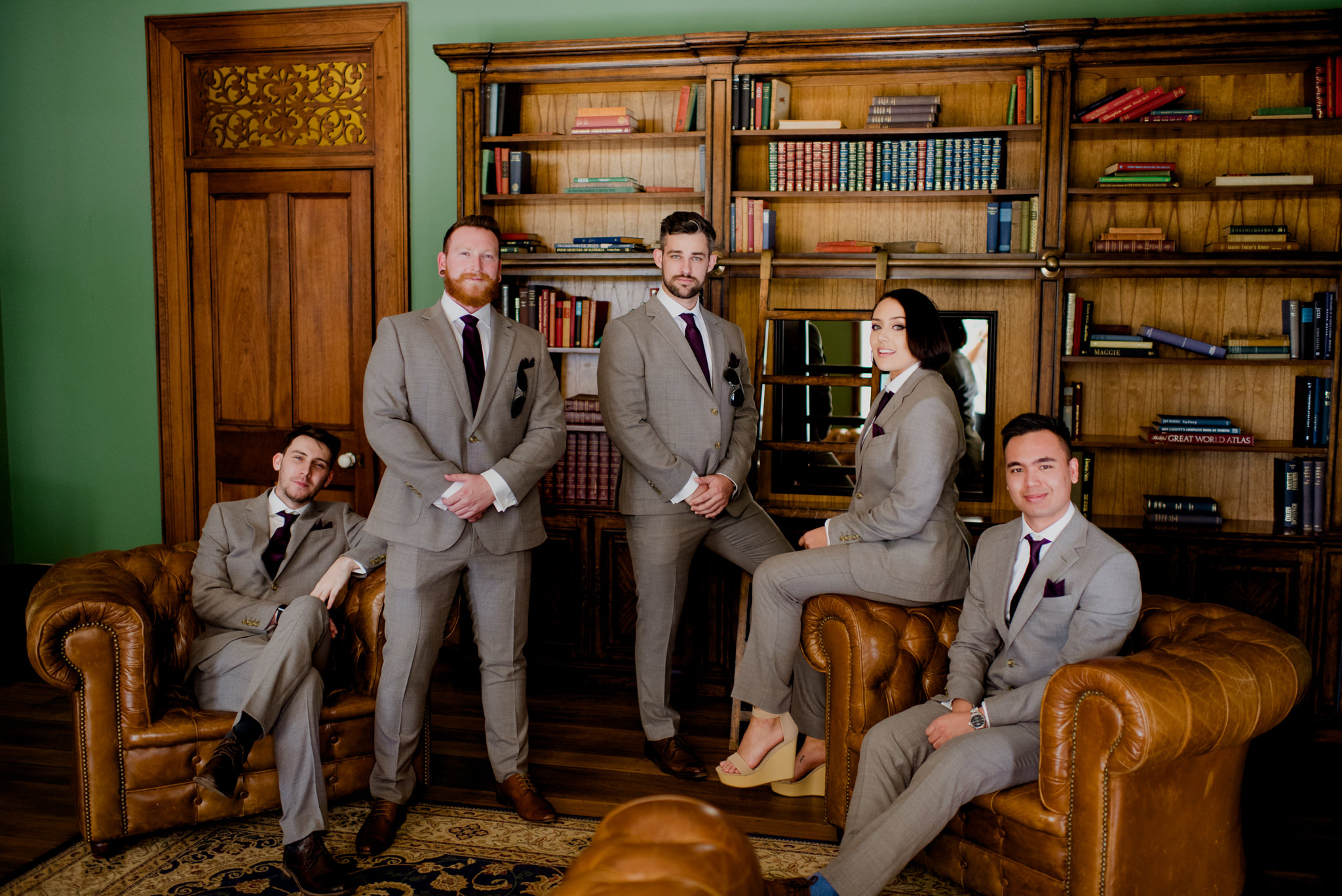 A groom and his groomsmen sitting in a library on leather chairs