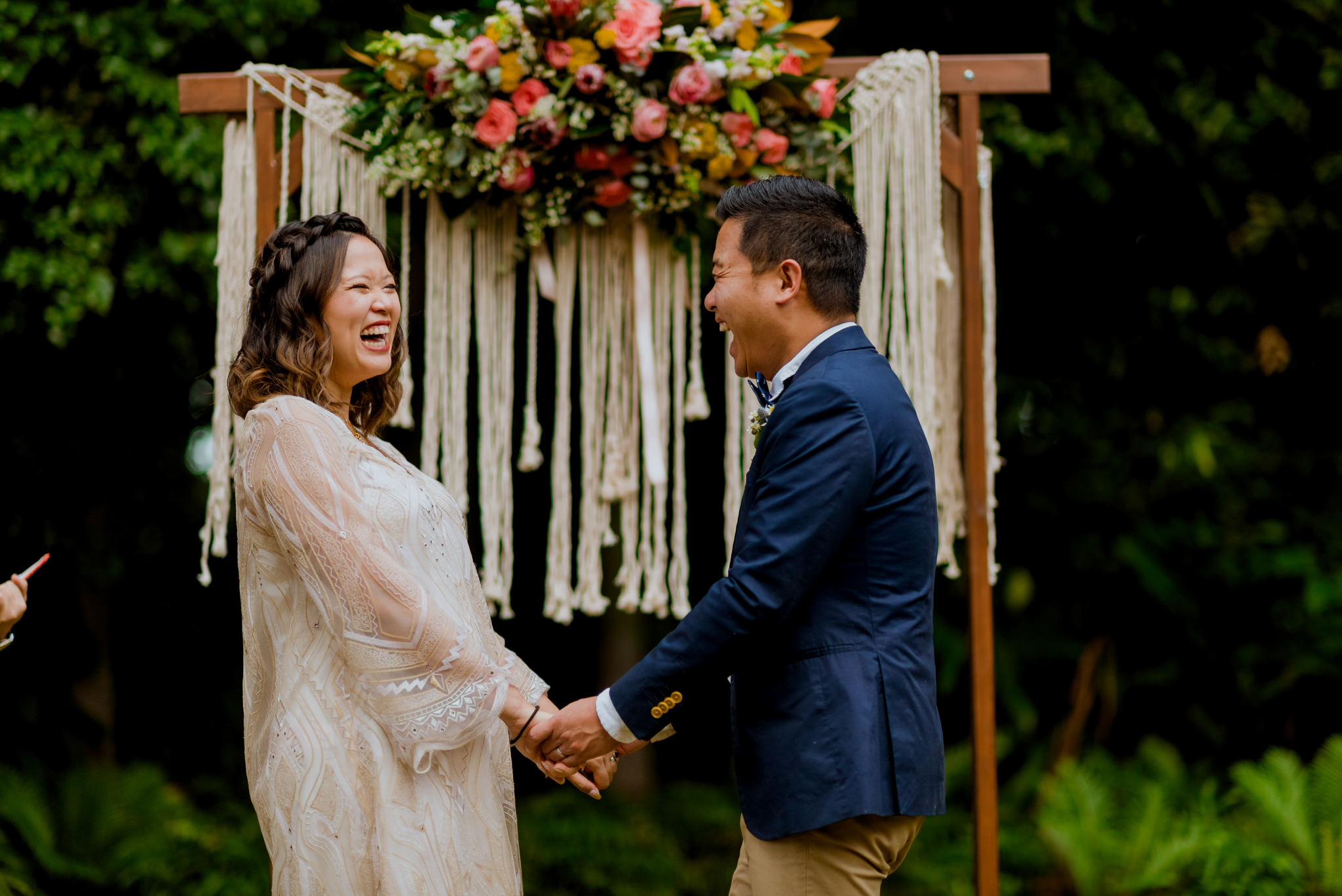 An asian bride and groom hold hands and laugh during their wedding ceremony
