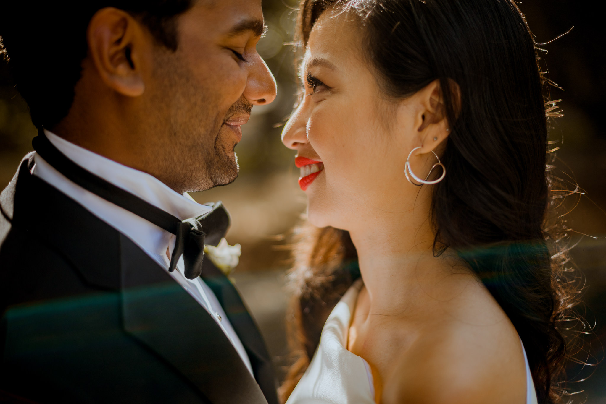An asian bride smiles and closely stares at her husband