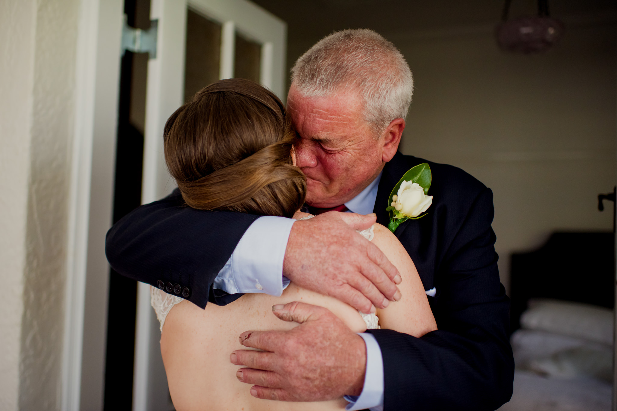A father cries as he hugs his daughter in her wedding dress
