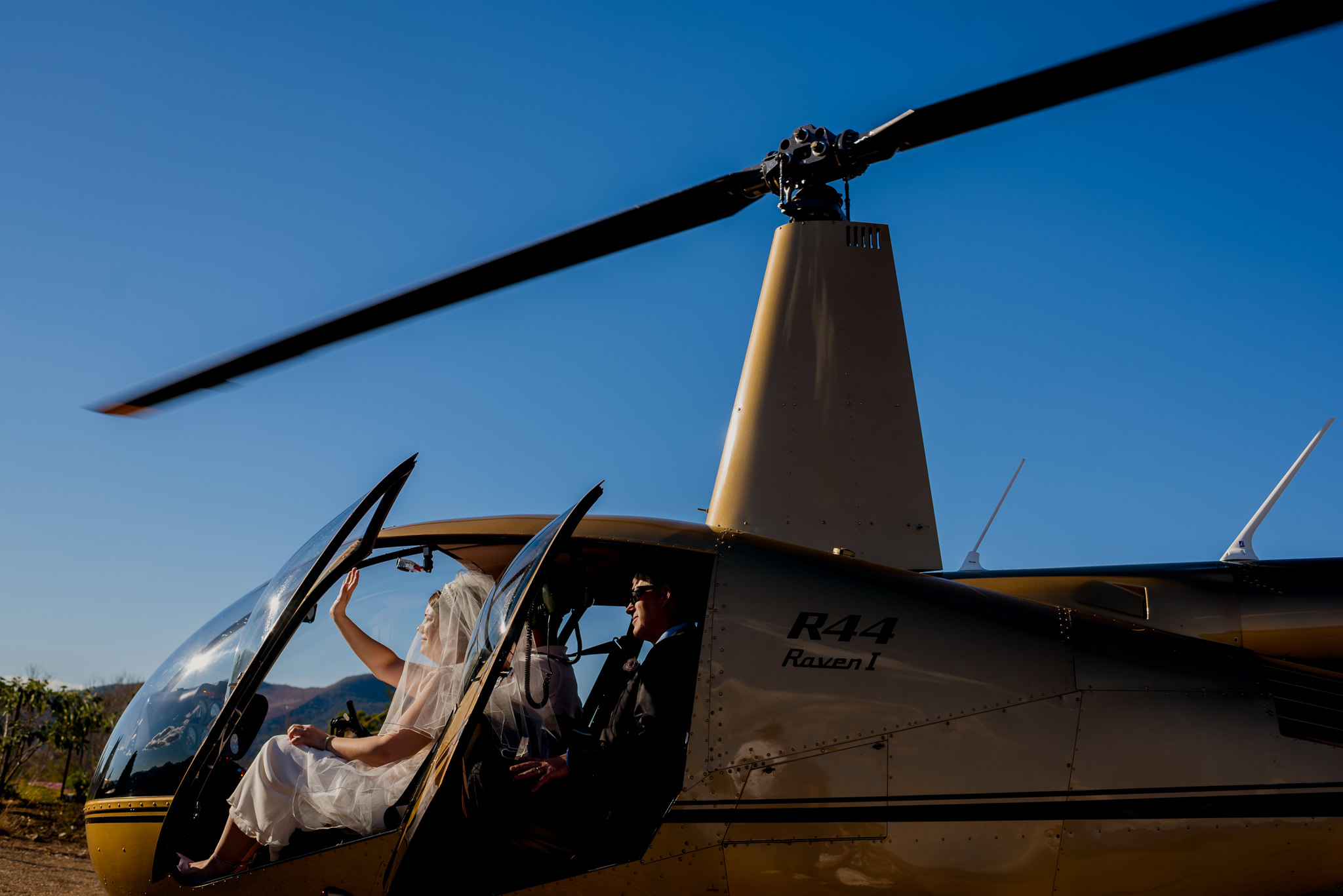 A bride in the cockpit of a landed helicopter waves