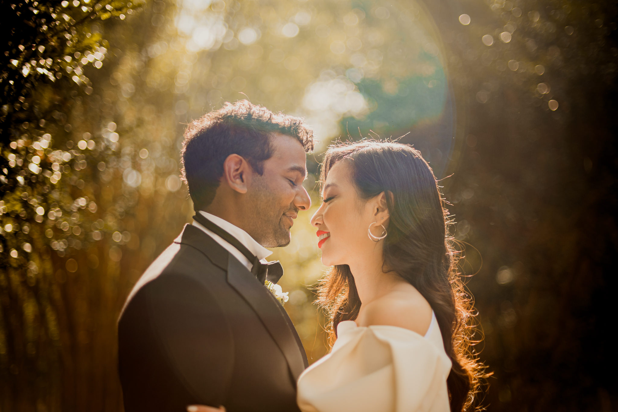 A interracial married couple stand facing each other in the sunlight with their eyes closed