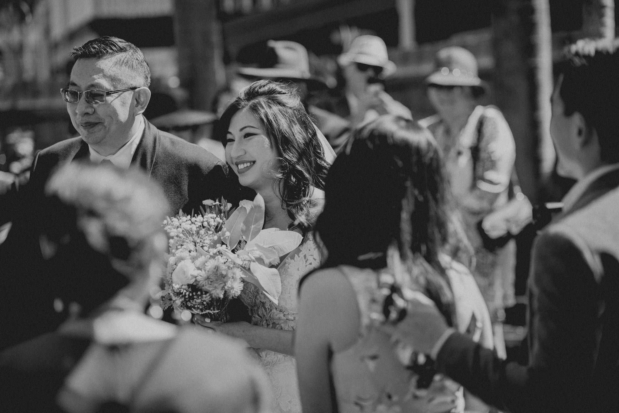 An asian bride smiles as her father walks her down the aisle