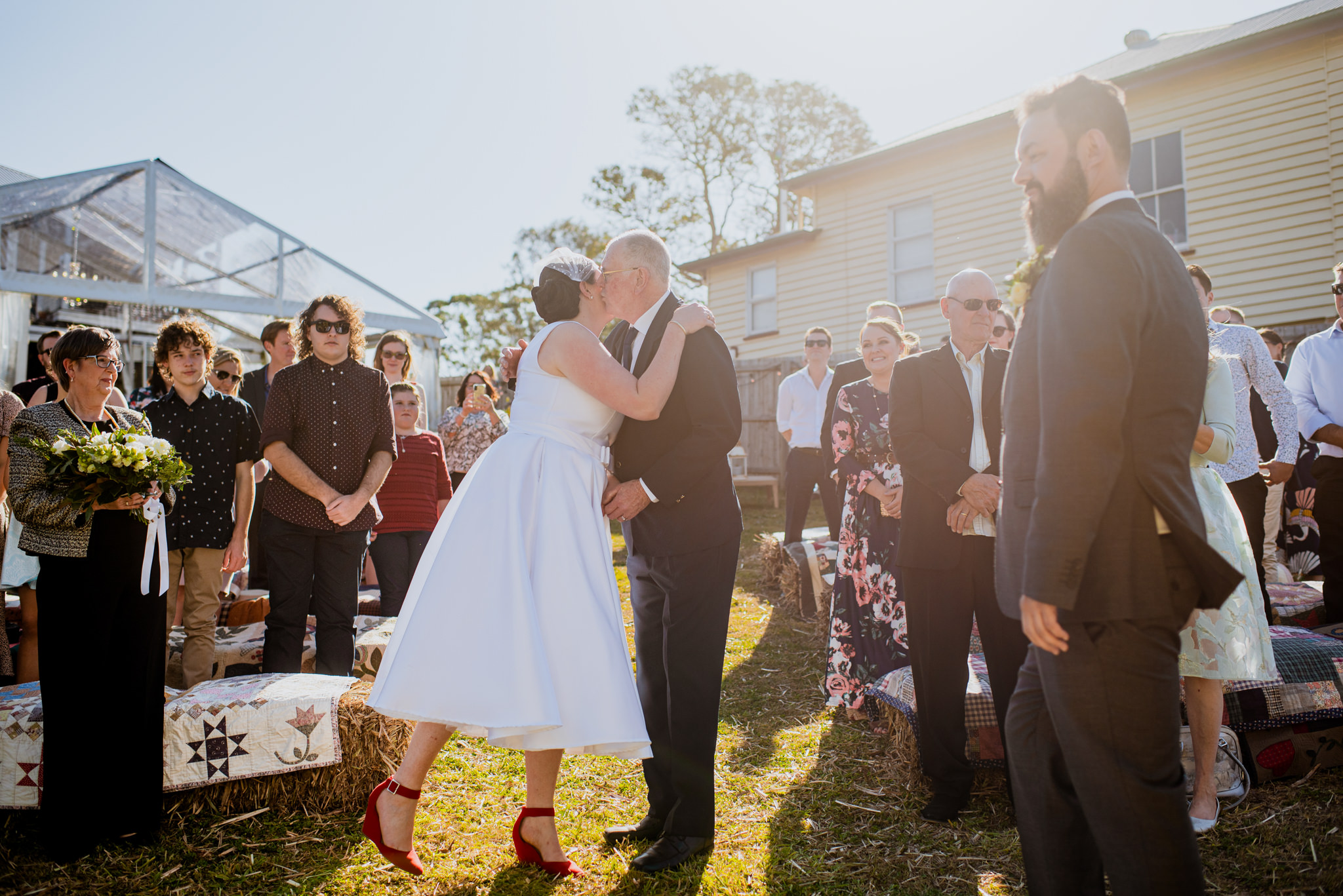 A bride kisses her father on the cheek as he walks her down her wedding aisle