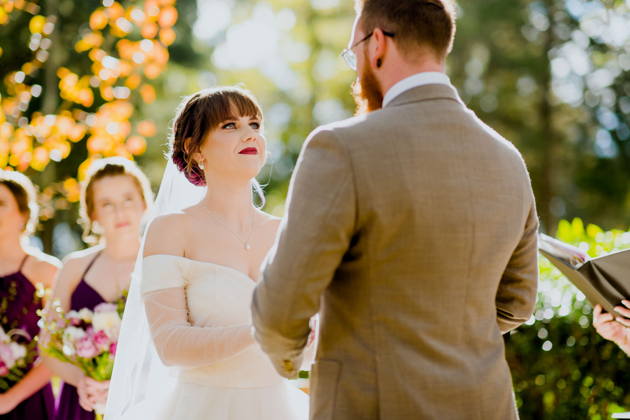 A bride smiles at her groom in anticipation during her outdoor wedding ceremony