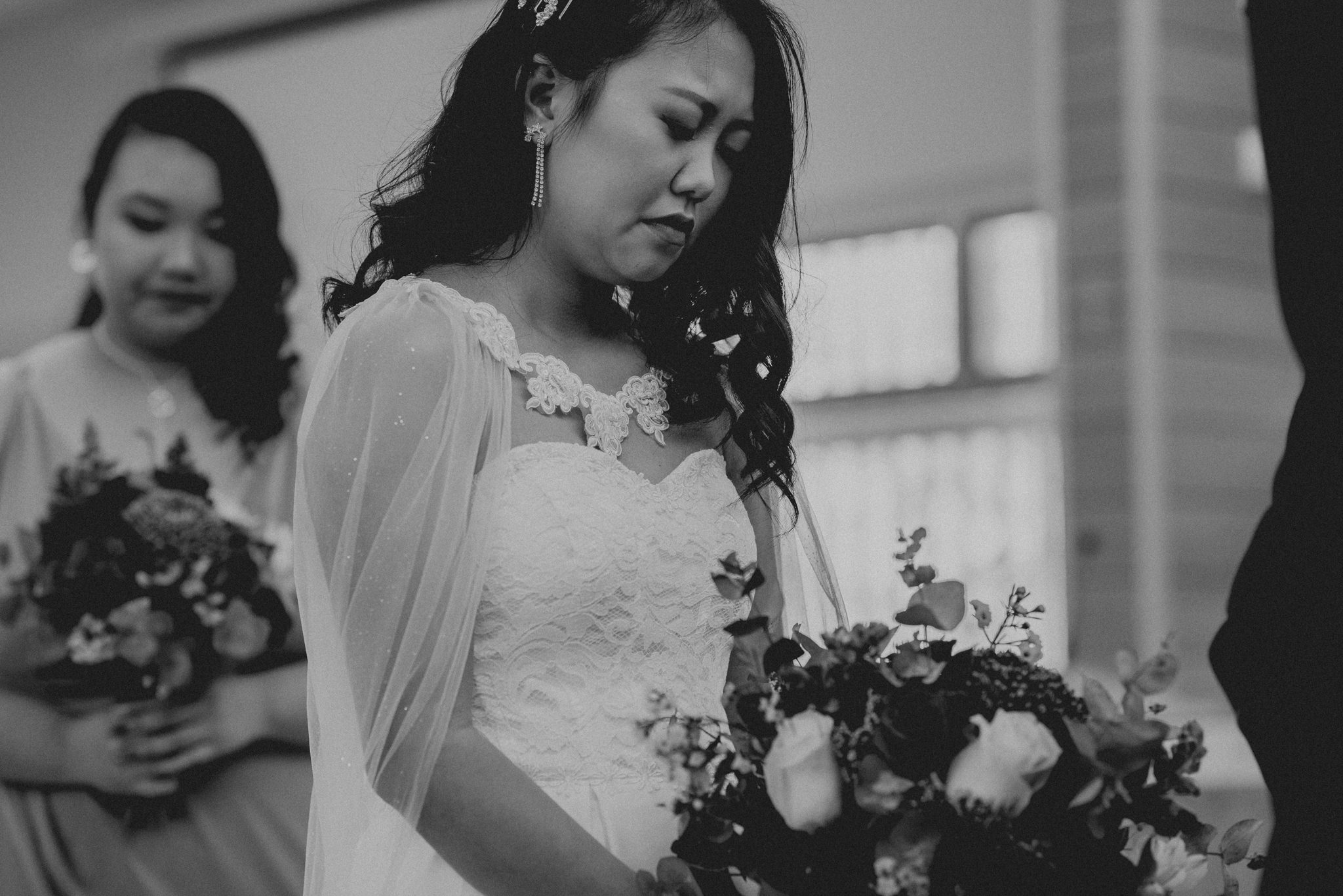 An asian bride closes her eyes and bows her head during her wedding ceremony