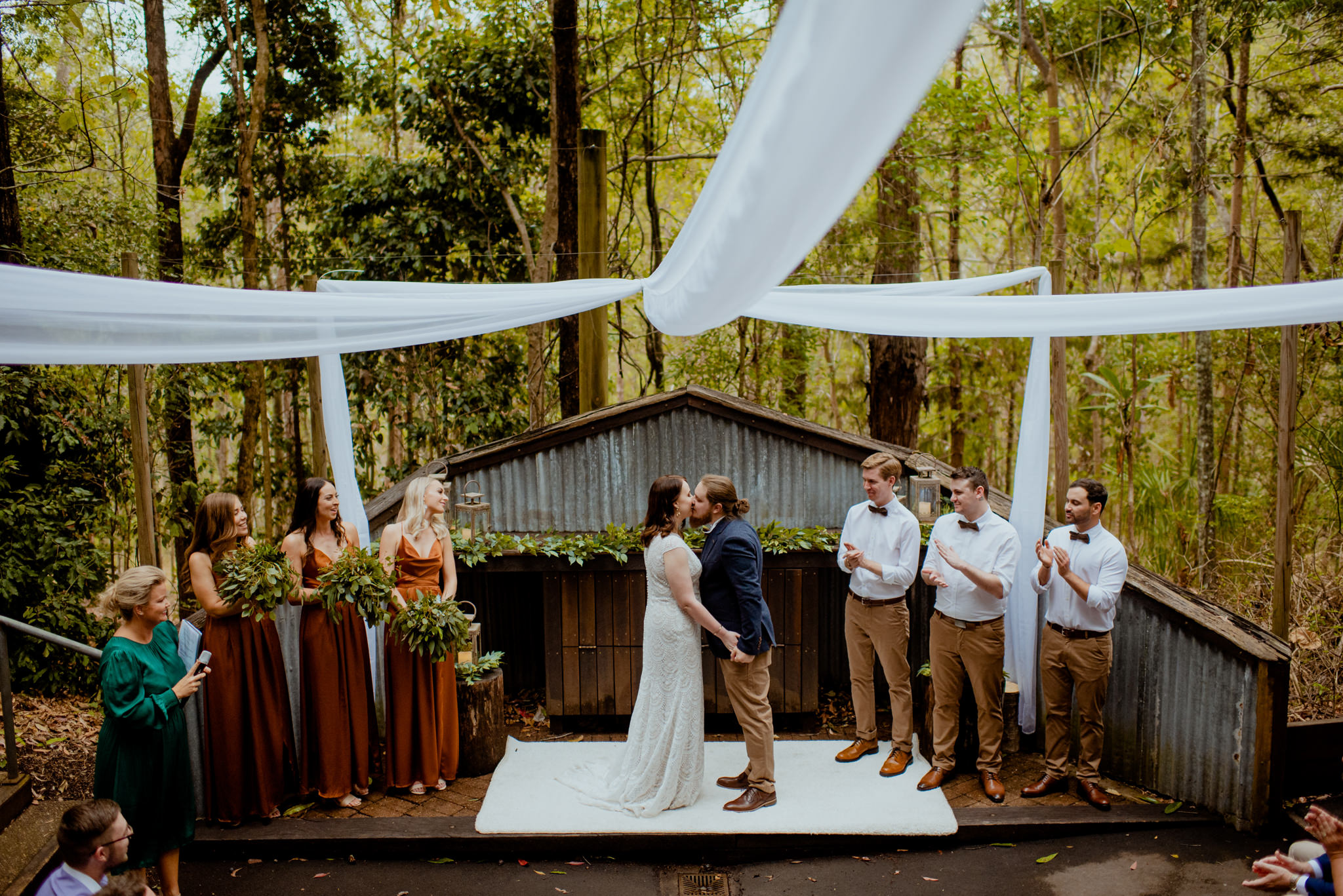 A bride and groom kiss at the end of their wedding ceremony in an Australian bush forest