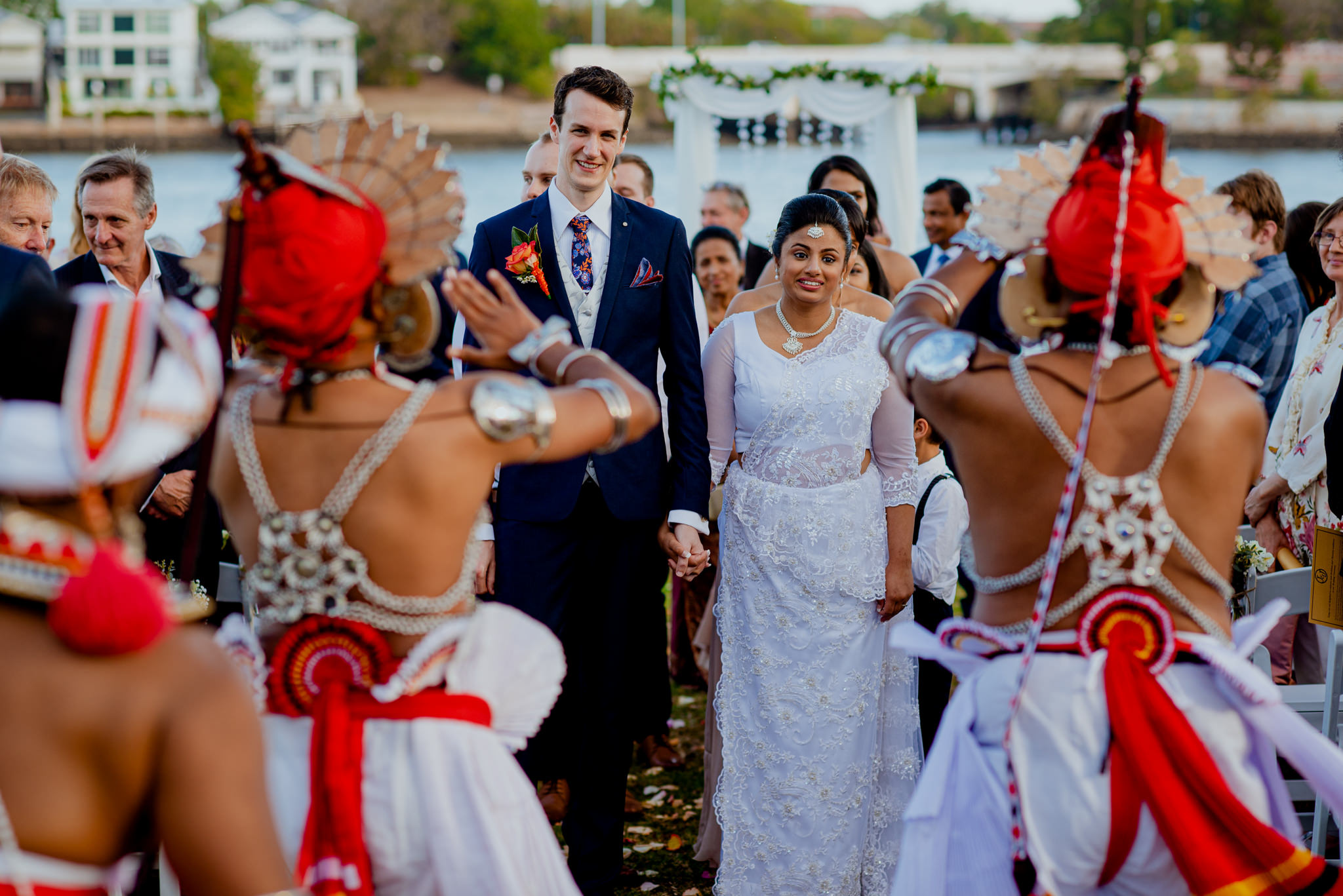 A bride and groom walk down the aisle together in front of Sri-Lankan dancers