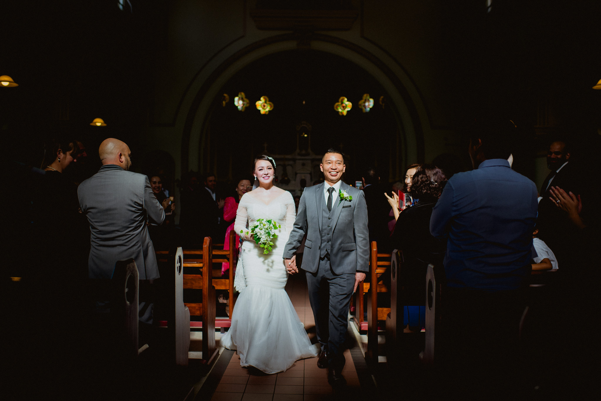 A bride and groom walk through a ray of sunlight in a dark church