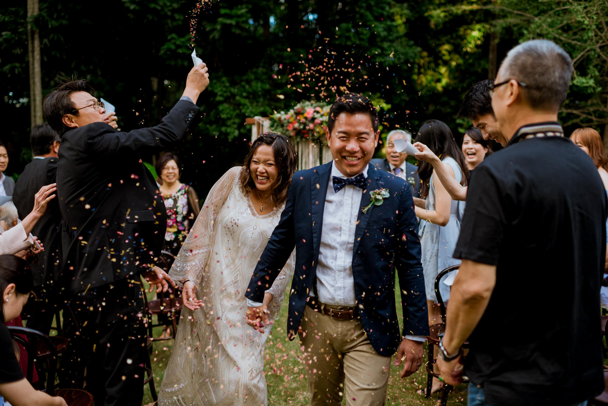 An asian bride and groom laugh as their guests throw confetti on them