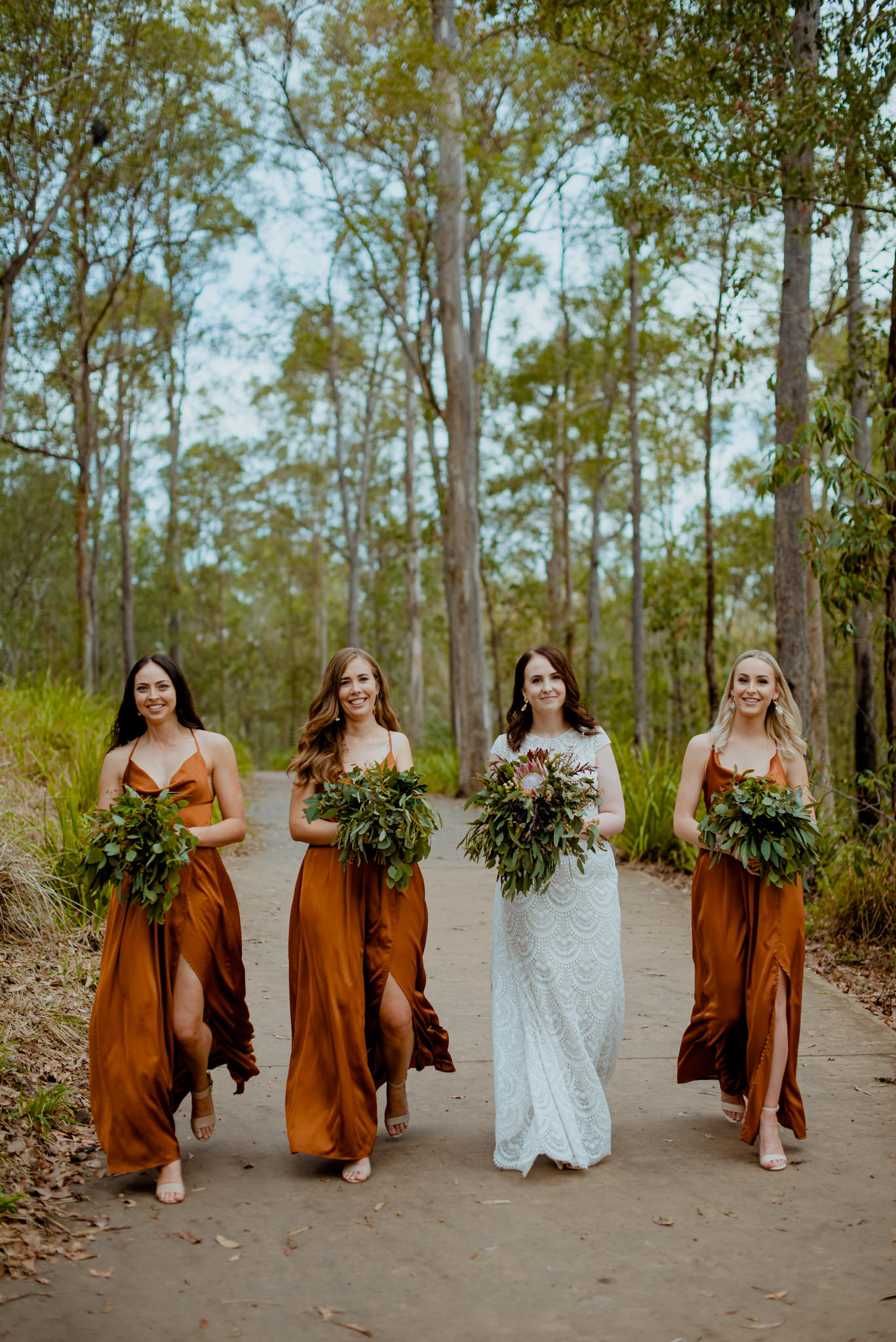 Bridesmaids in orange dresses walk down a path with a happy bride