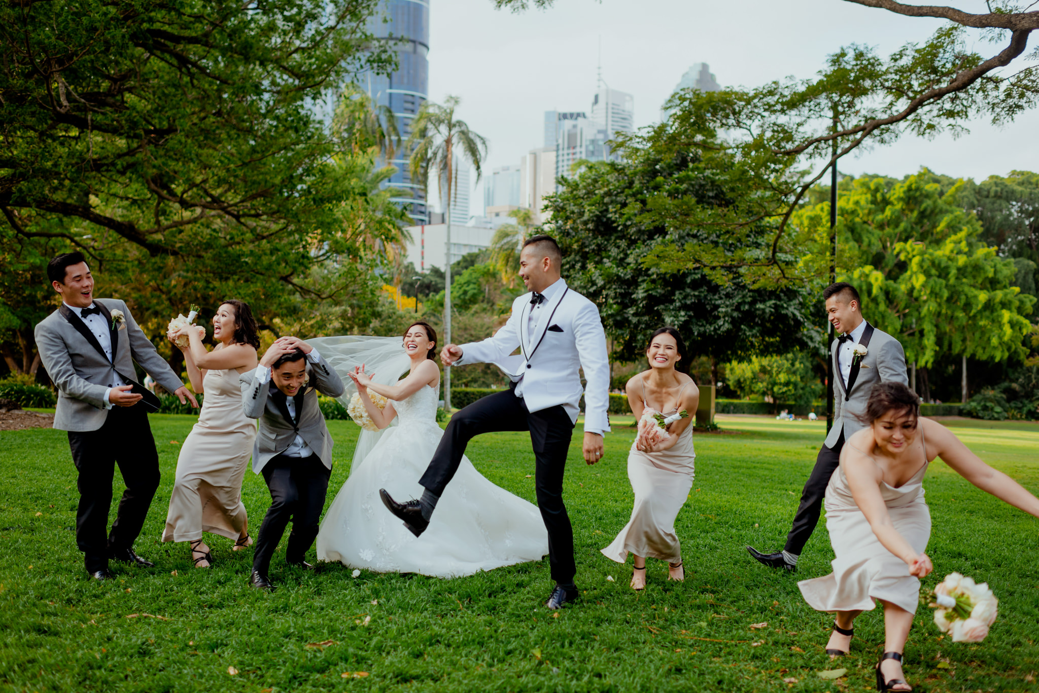 A chaotic group photo of a bridal party catching bouquets