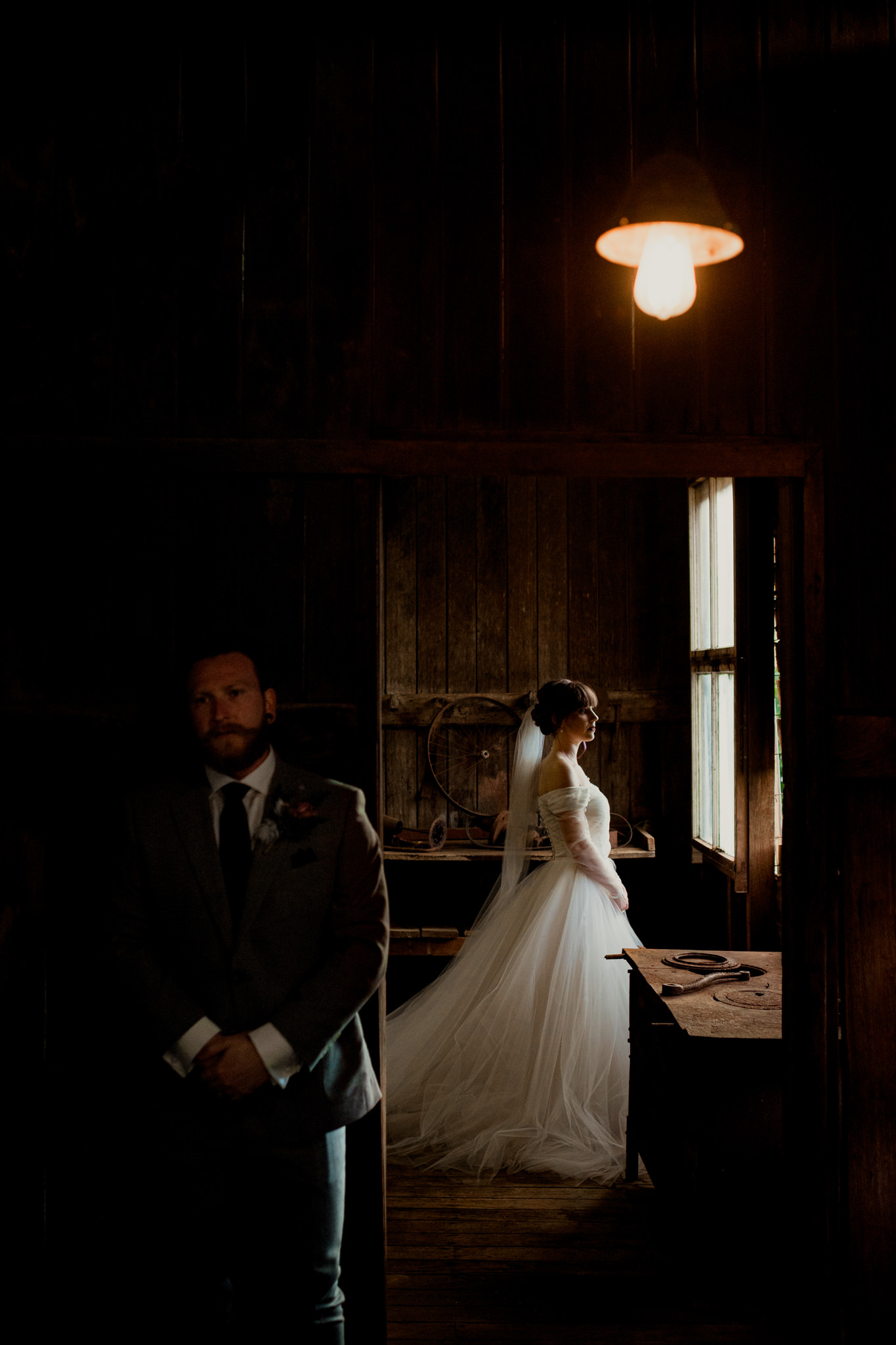 A groom waits patiently outside a room as his bride is illuminated by a windowsill