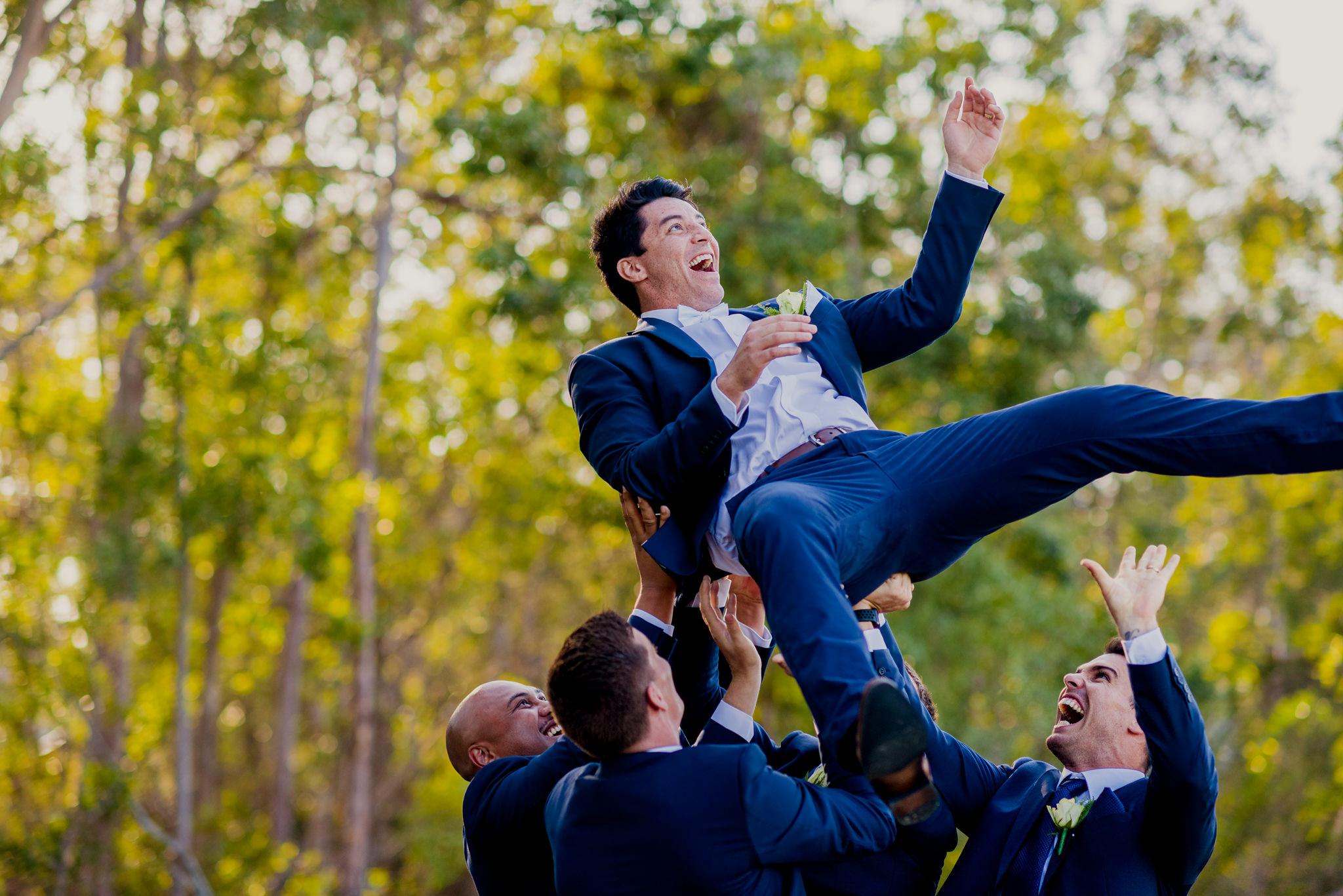 A group of groomsmen throw a newlywed groom in the air