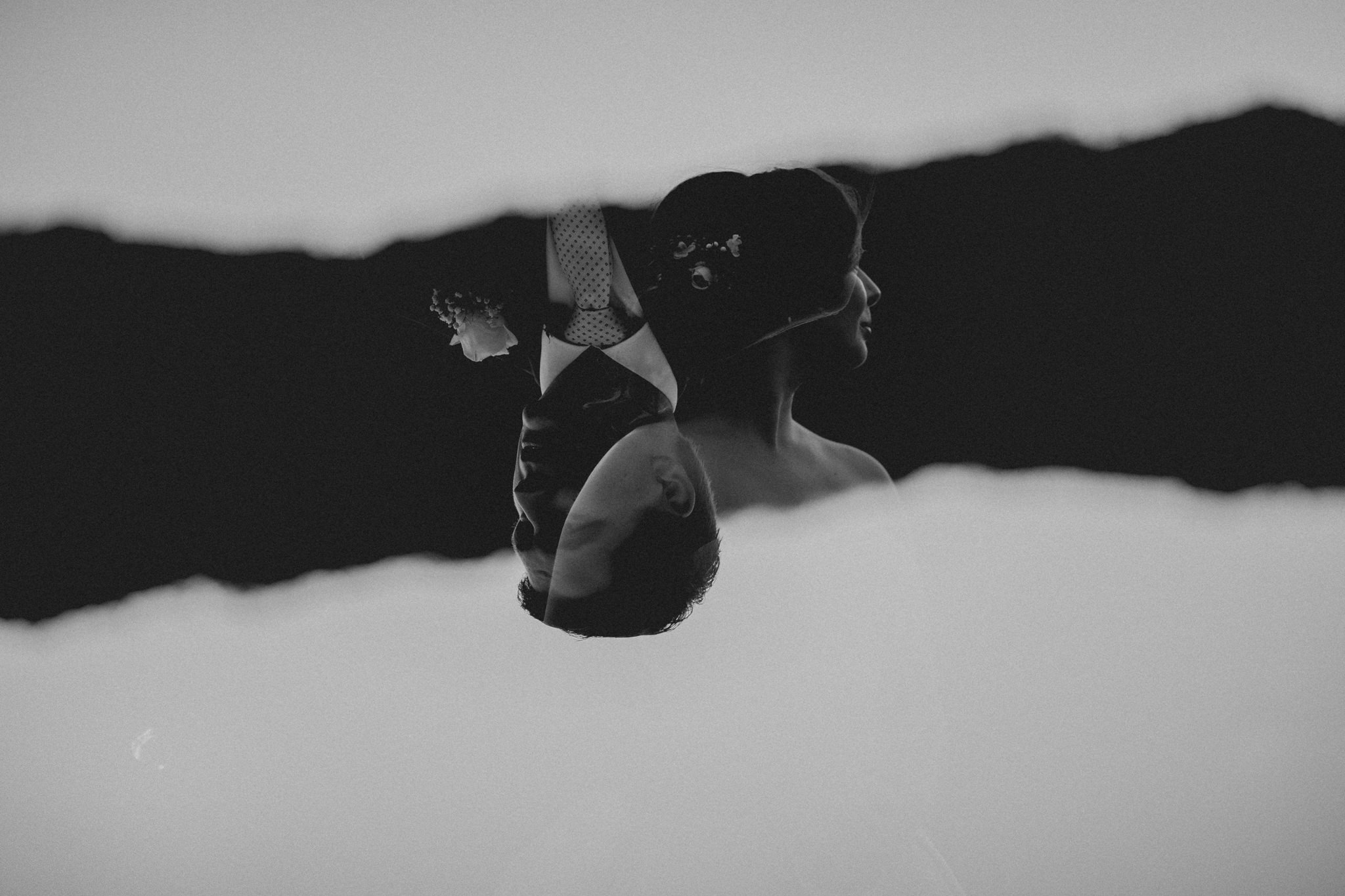 A double exposure of a bride and groom's face set against a mountain