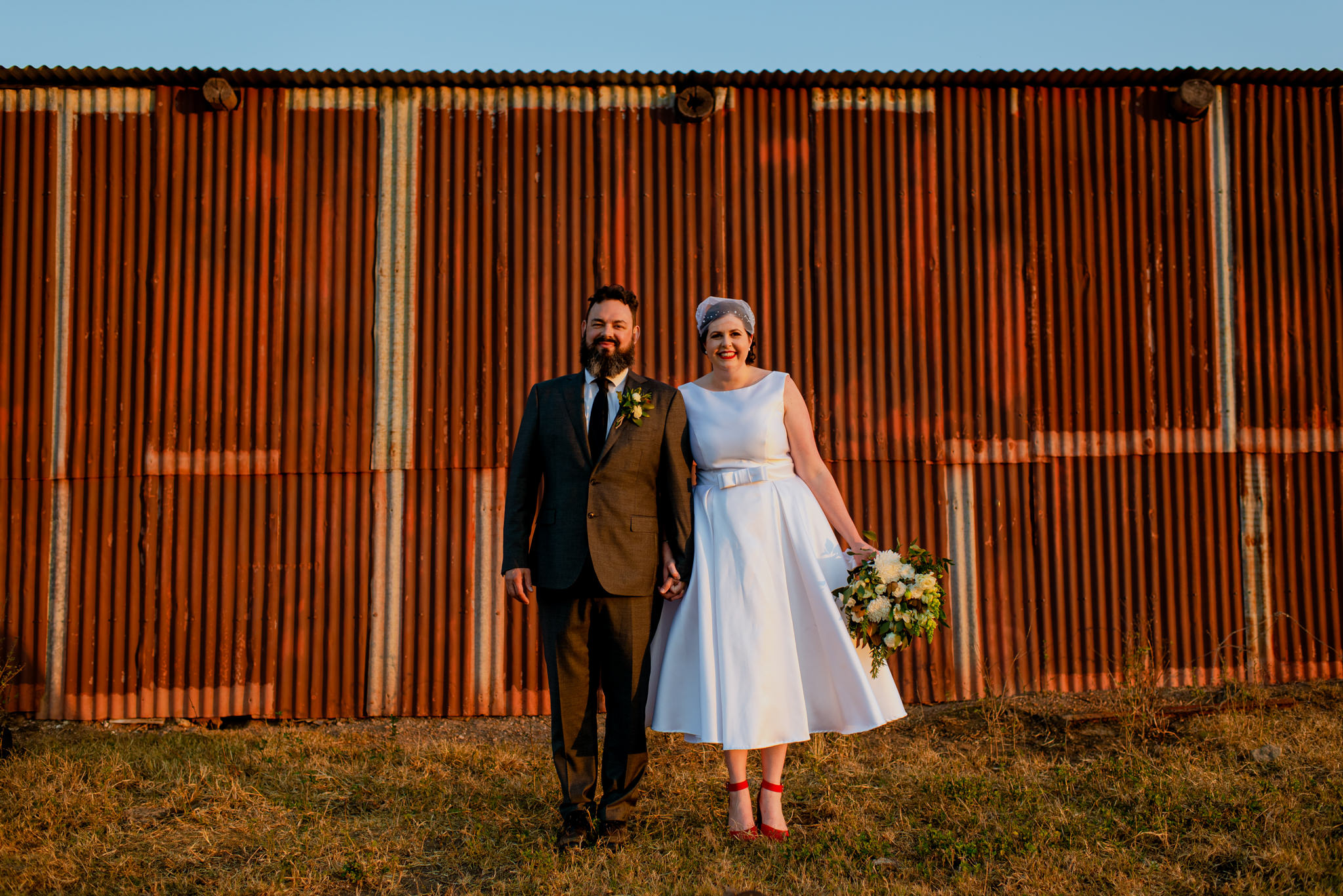 A bride and groom hold hands and laugh in front of a rusty iron shed