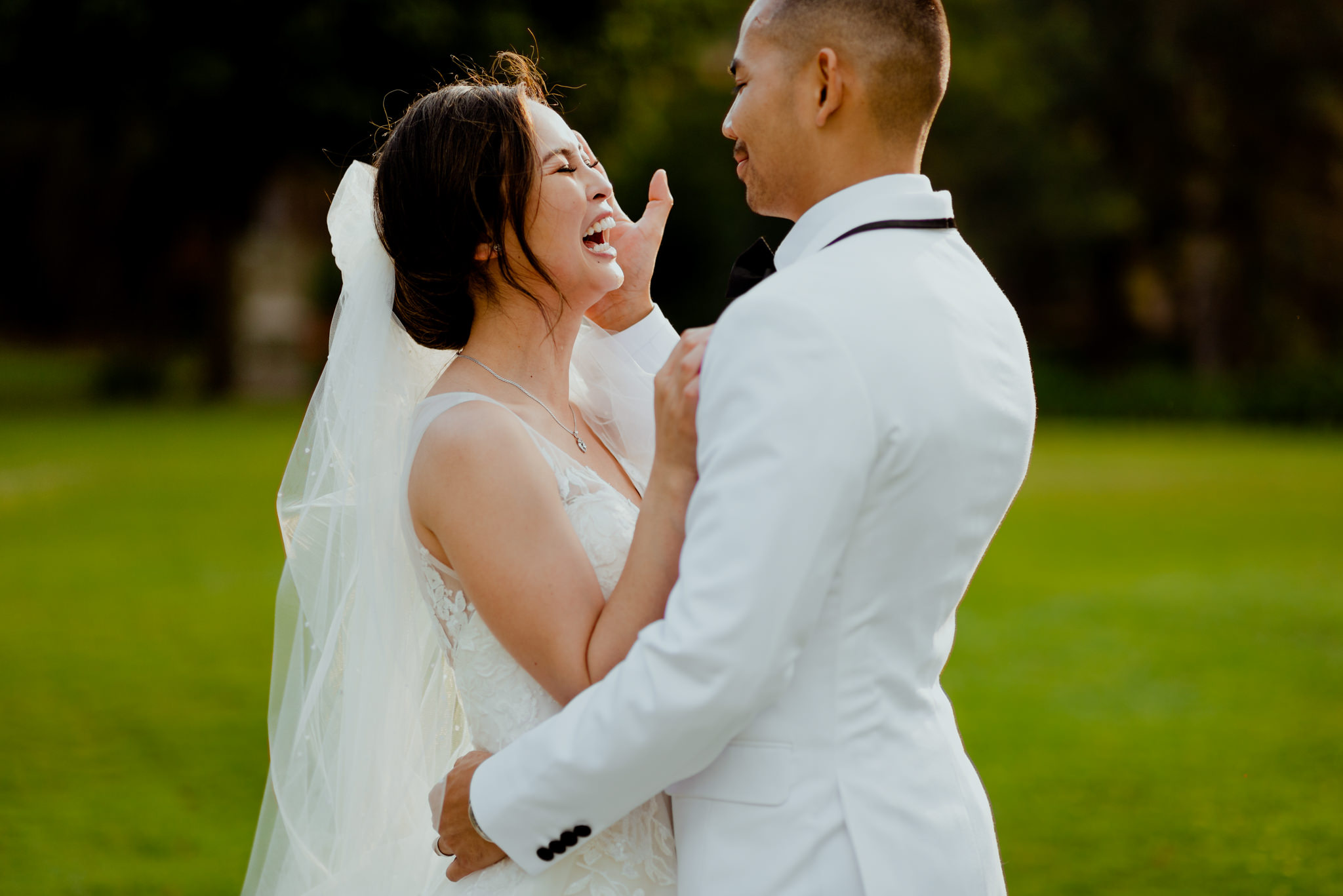 A bride laughs as her husband strokes her cheek