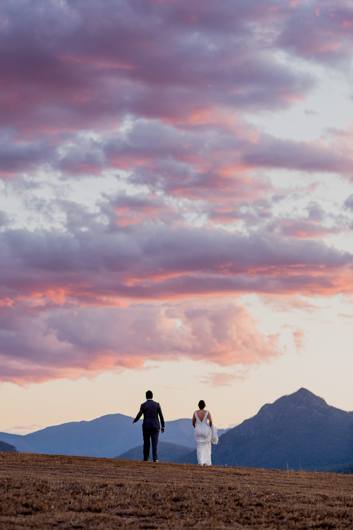A bride and groom walk over a hill against a pink sunset at Kooroomba Lavender Farm