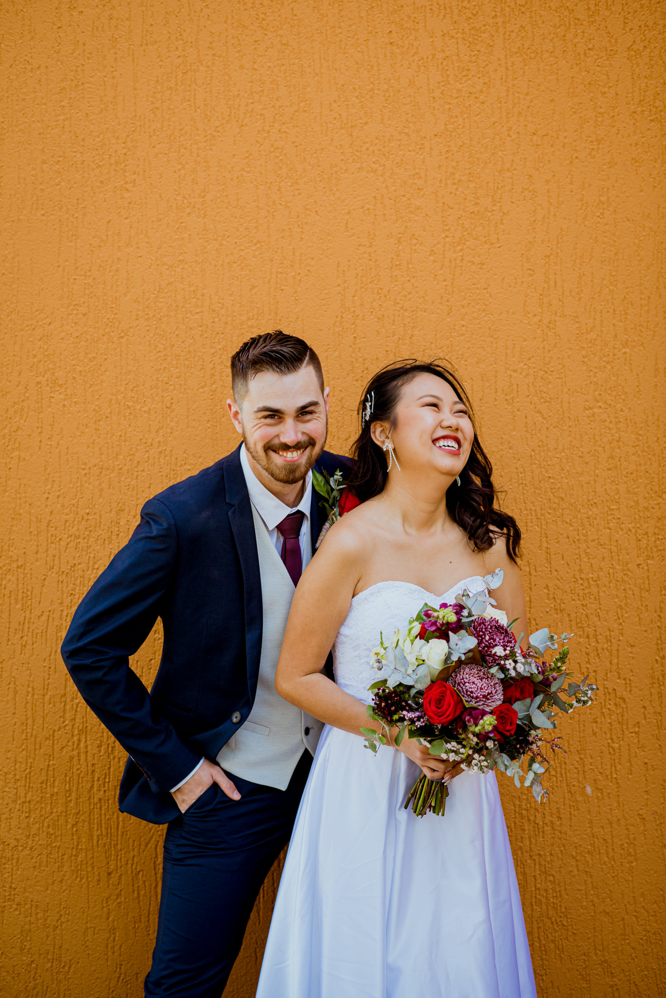 A young bride and groom laugh in front of an orange wall