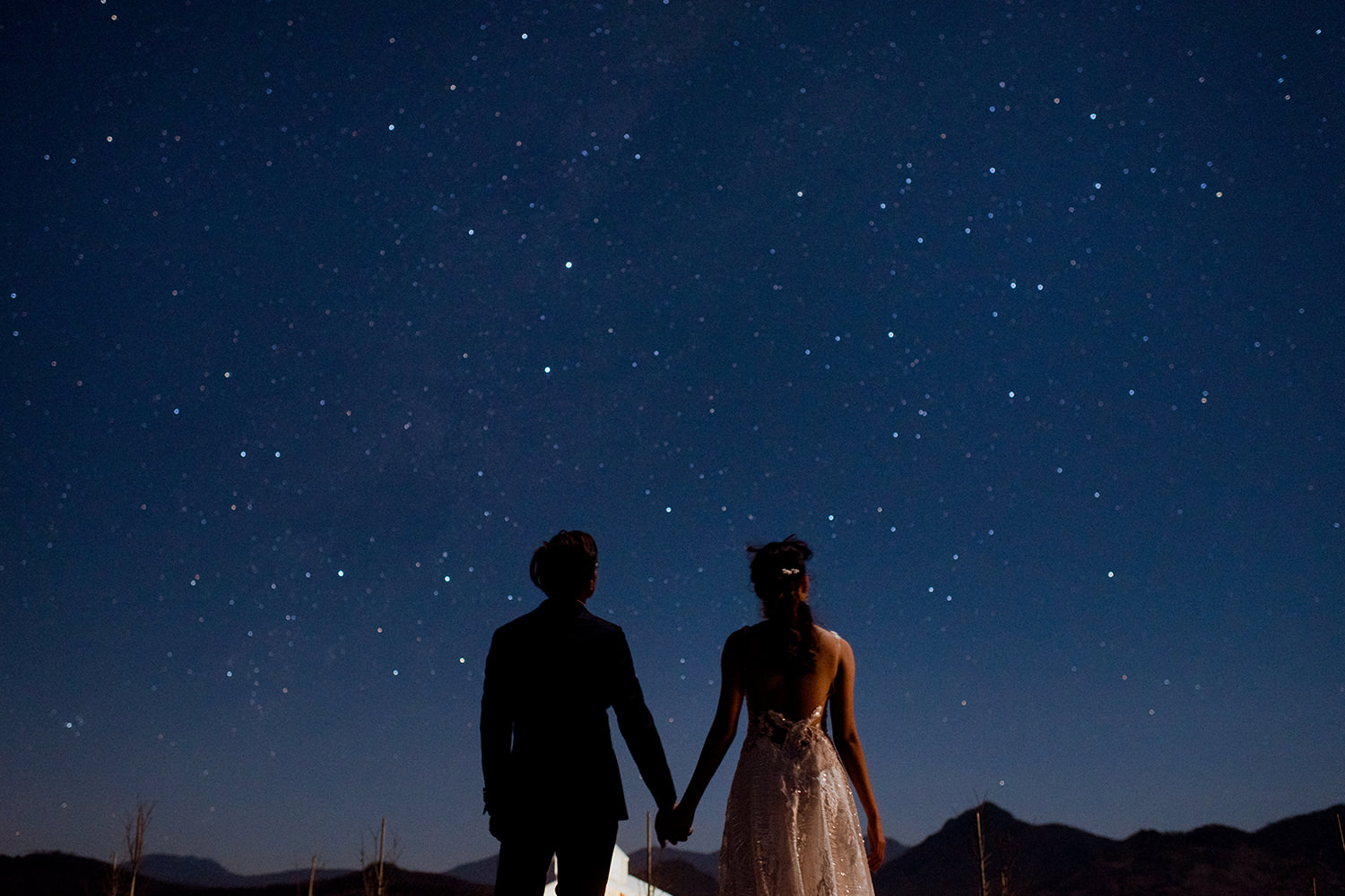 Newly married couple hold hands as they look at the starry night sky