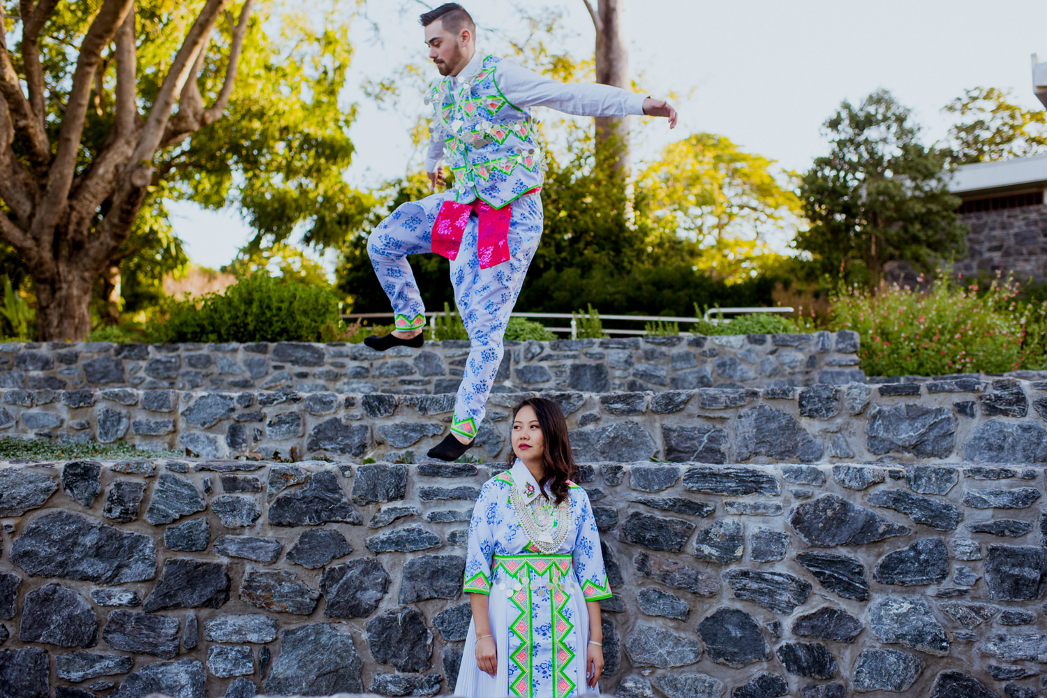Young man wearing traditional Hmong clothes hops over woman's head on a stone wall