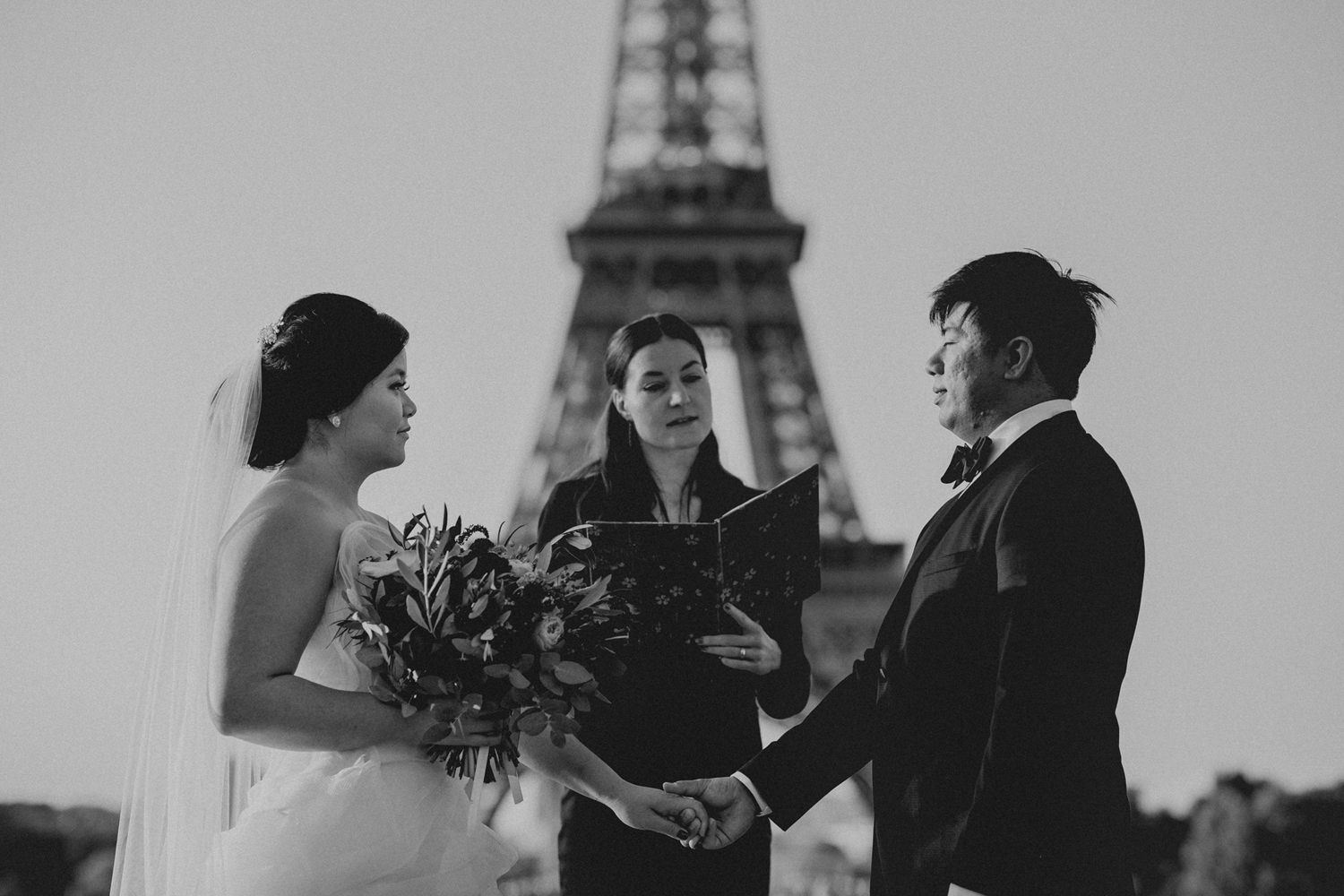 Asian bride and groom having a wedding ceremony in front of the Eiffel Tower