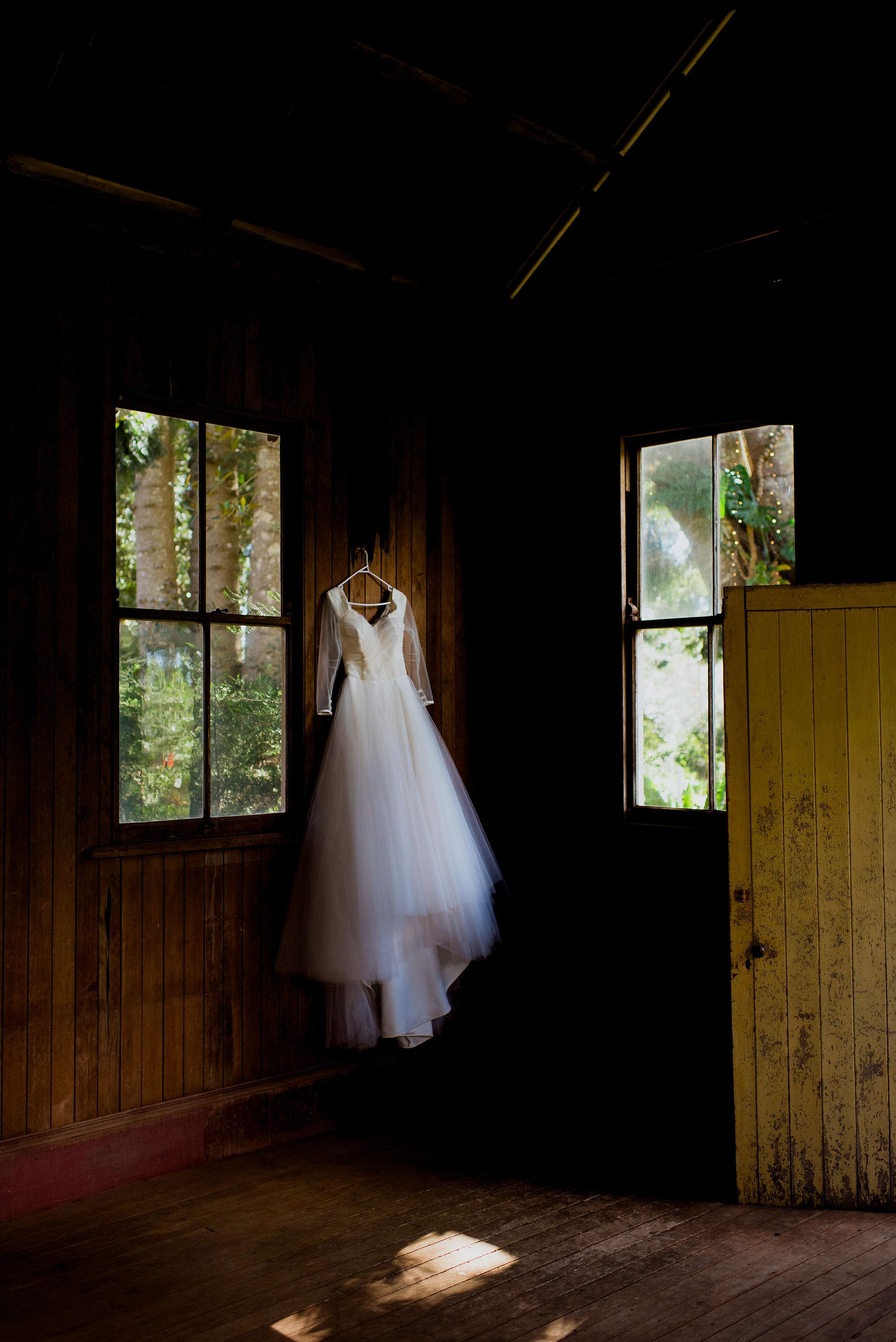 Wedding dress hanging in rustic wooden barn