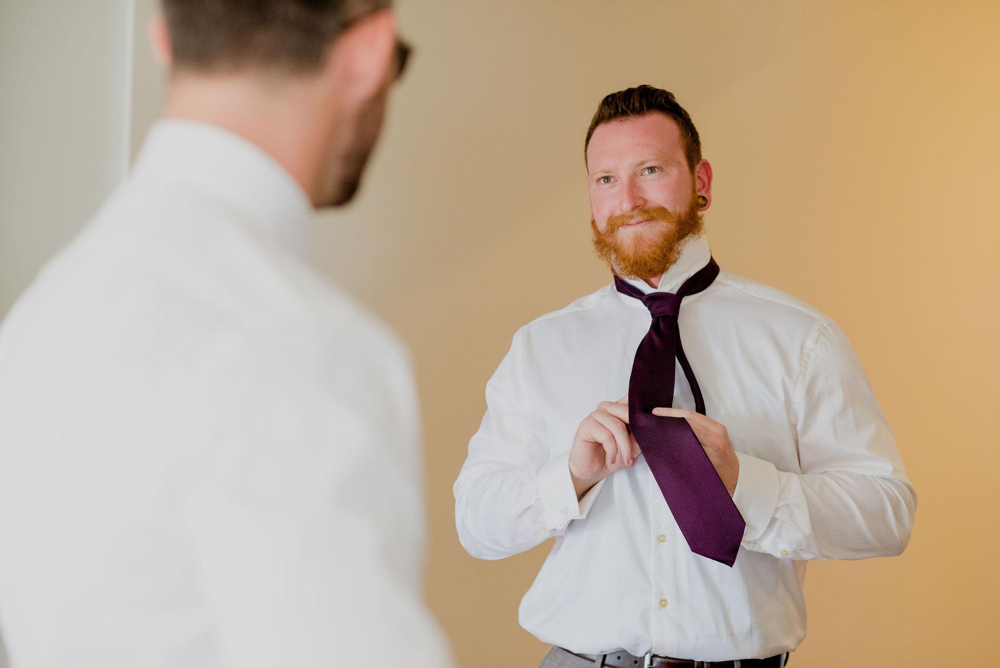 Bearded man tying his purple tie