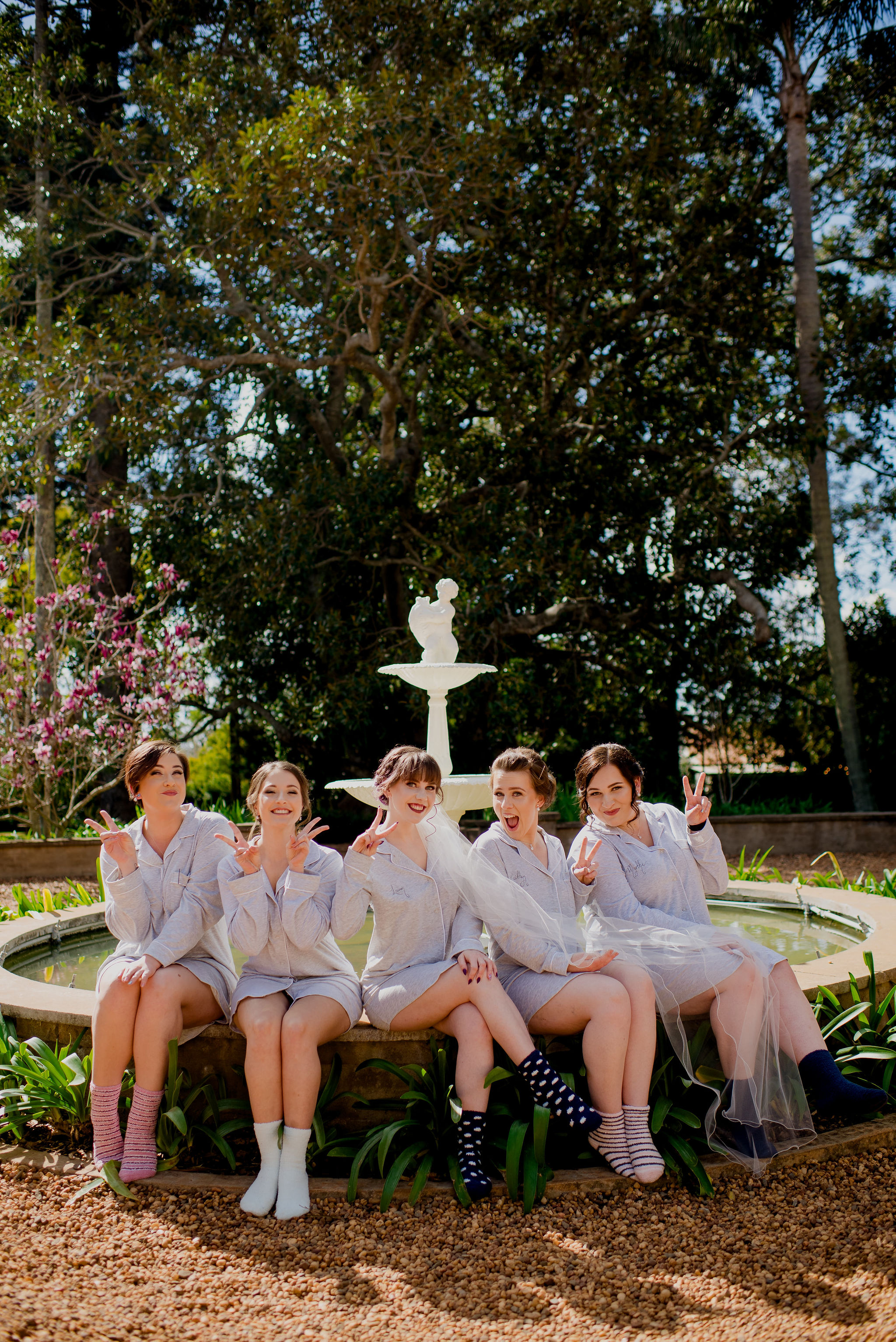 Bride-to-be and bridesmaids in pyjamas sitting on fountain