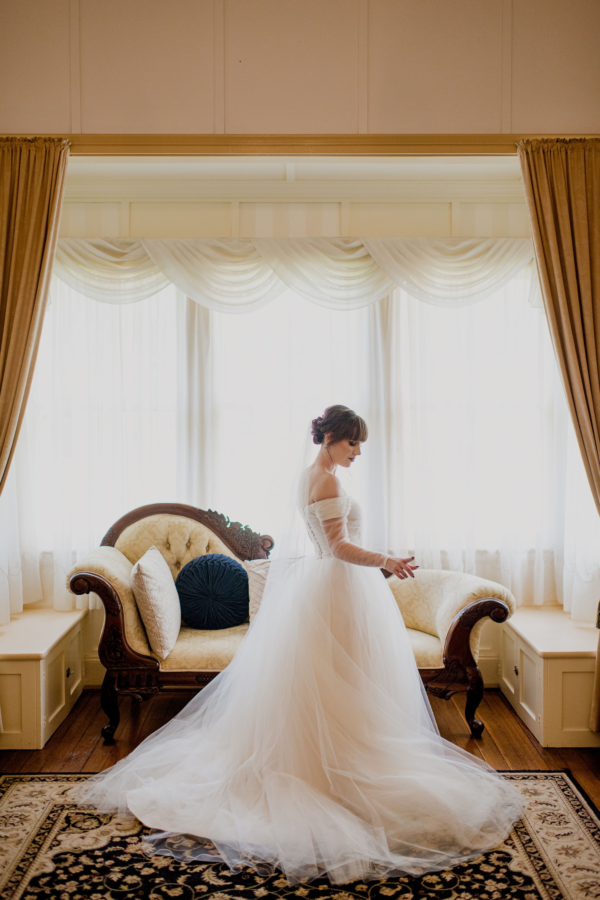 Bride in wedding dress posing in front of a large windowsill