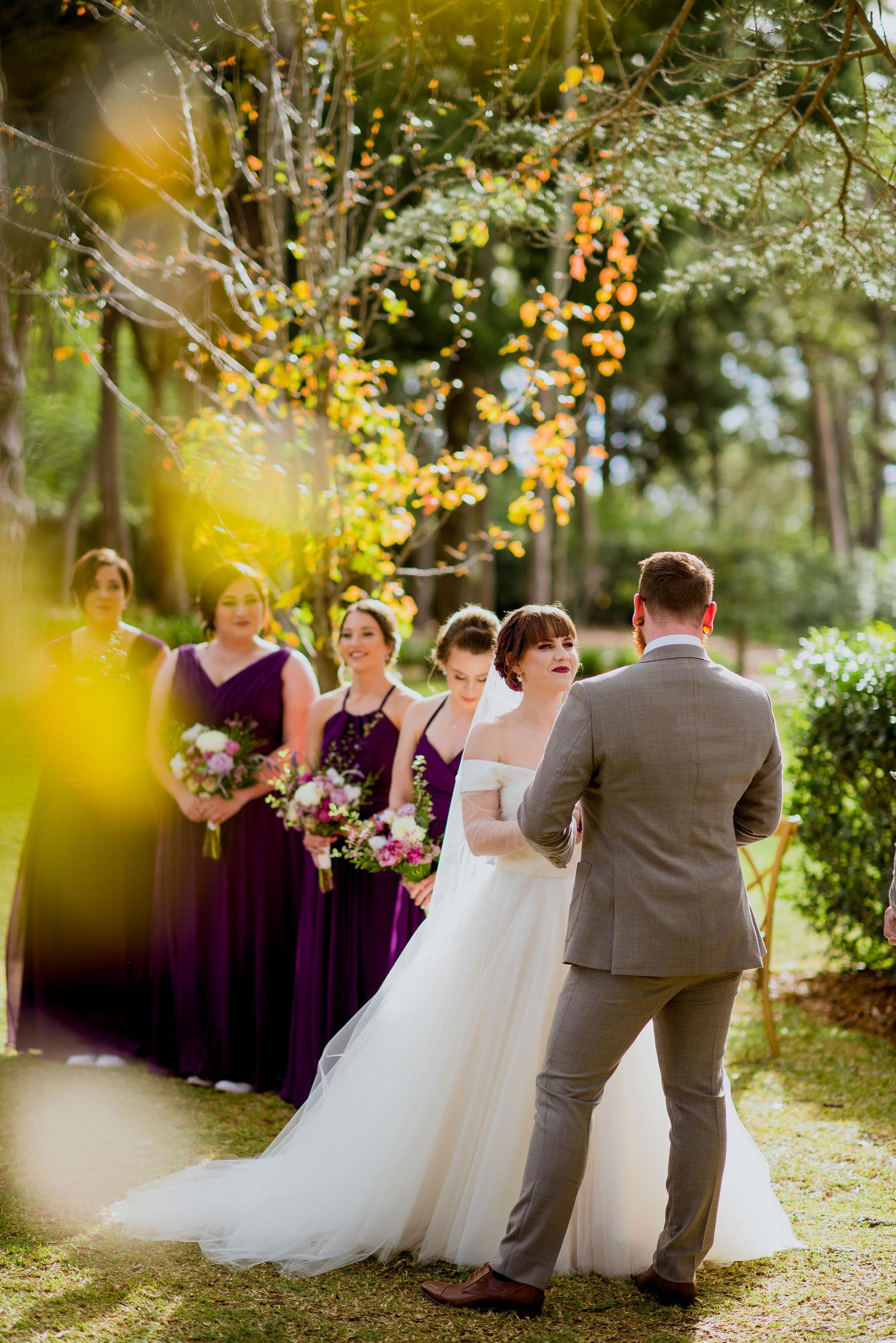 Bride smiling during her wedding vows in a garden