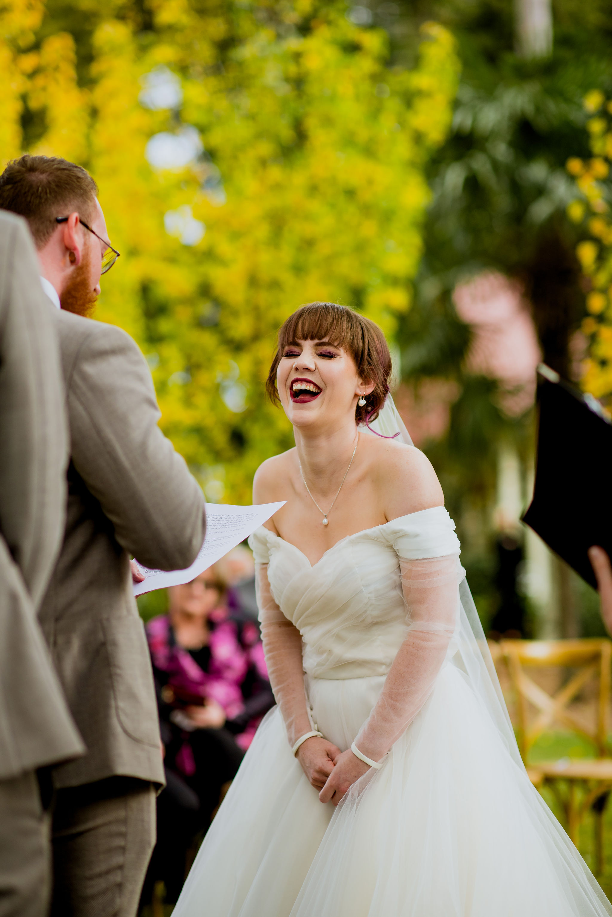Bride laughing during groom's wedding vows