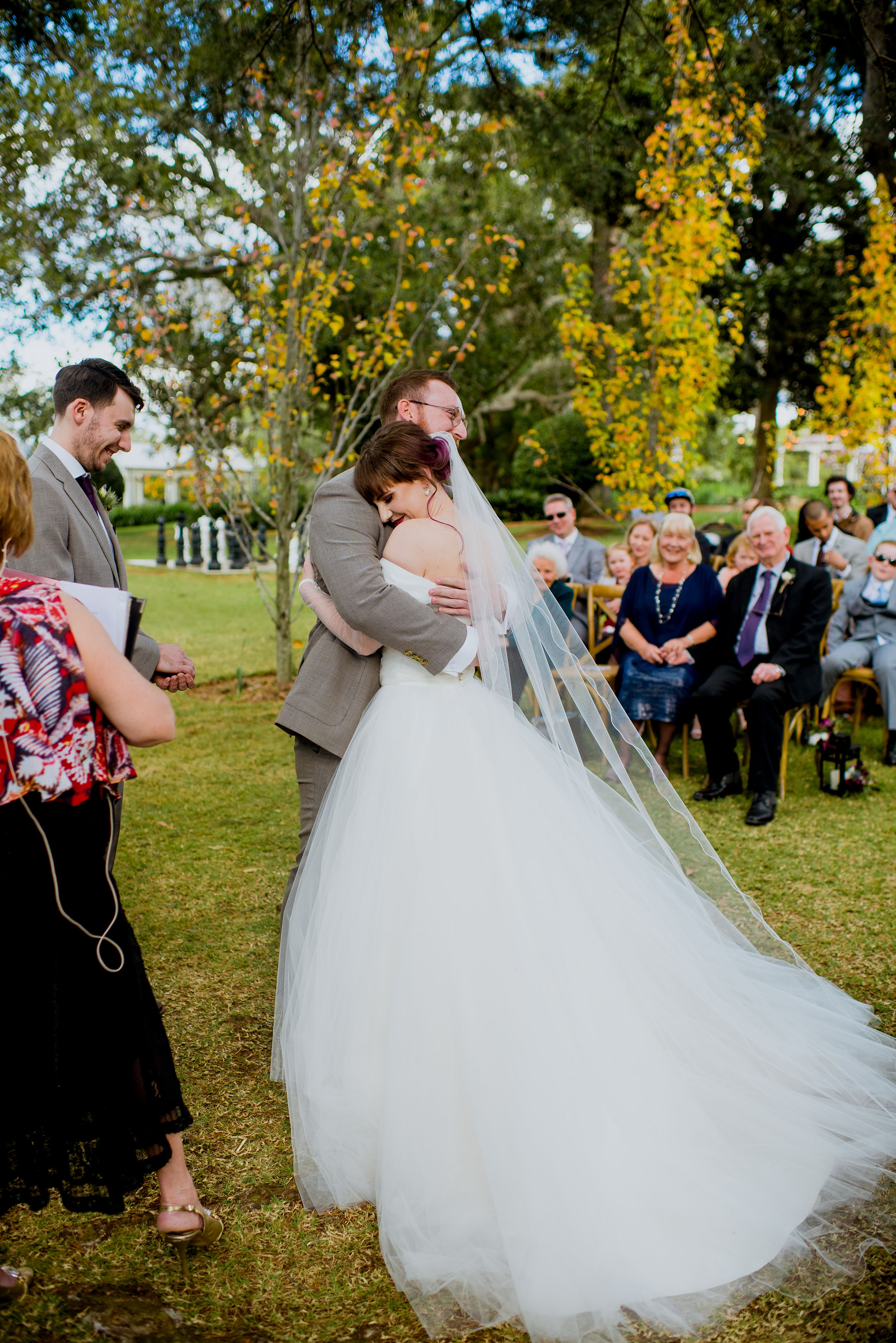 Bride and groom embracing happily at an outdoor garden wedding ceremony