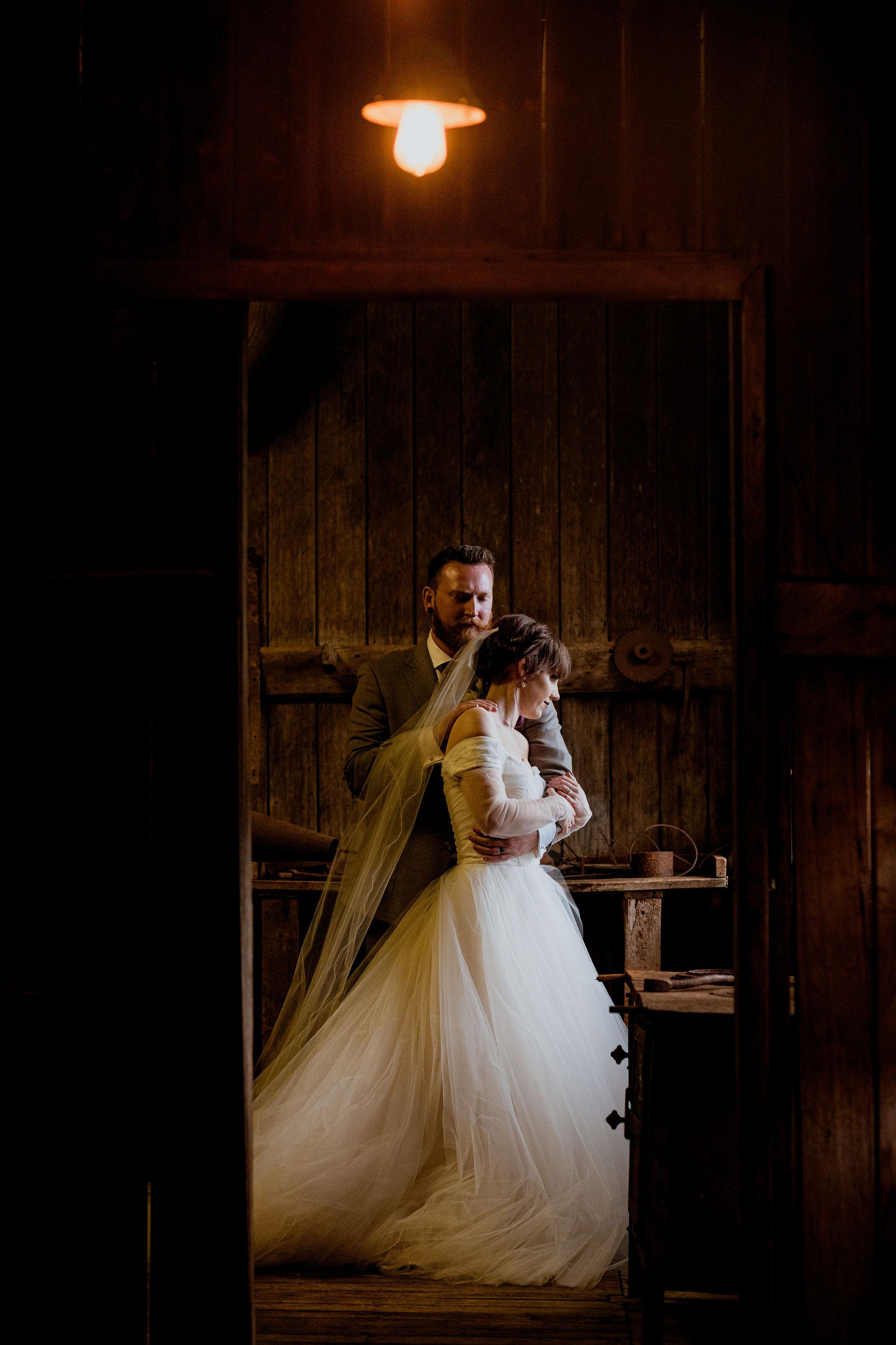 Bride and groom hugging in a rustic wooden workshop