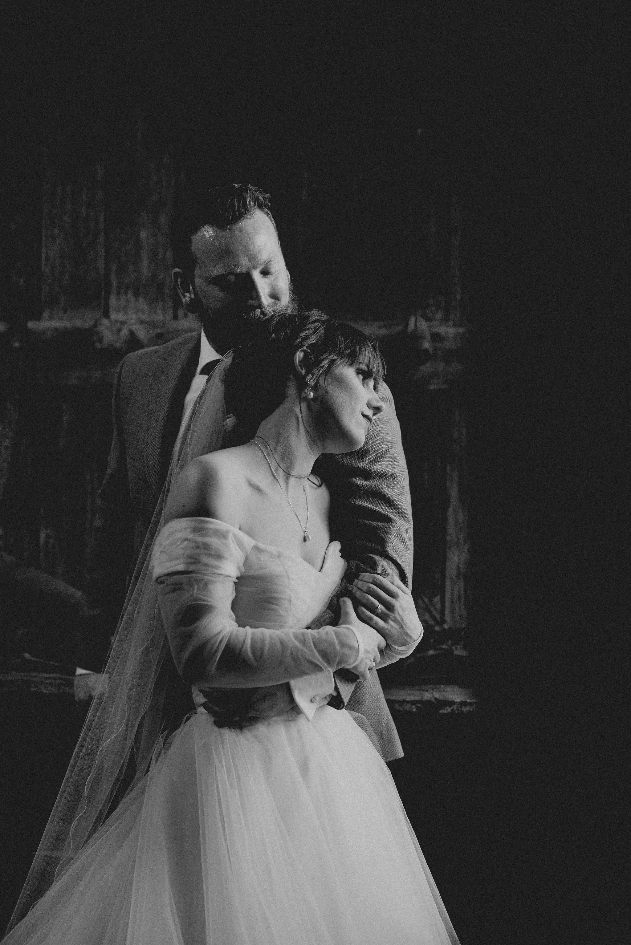 Bride and groom hugging in a rustic wooden workshop in black and white