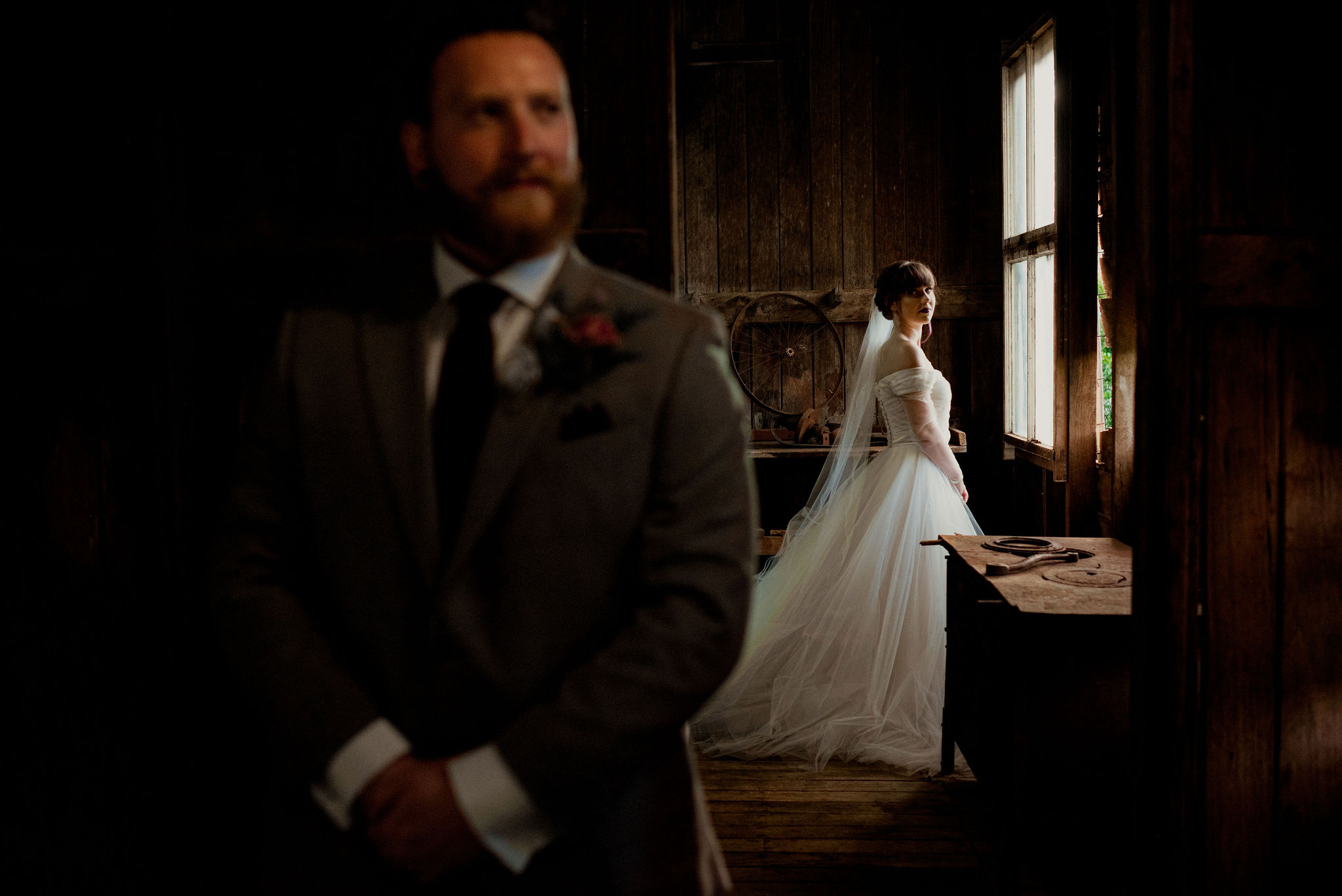 Bride and groom posing in different rooms in a rustic wooden workshop