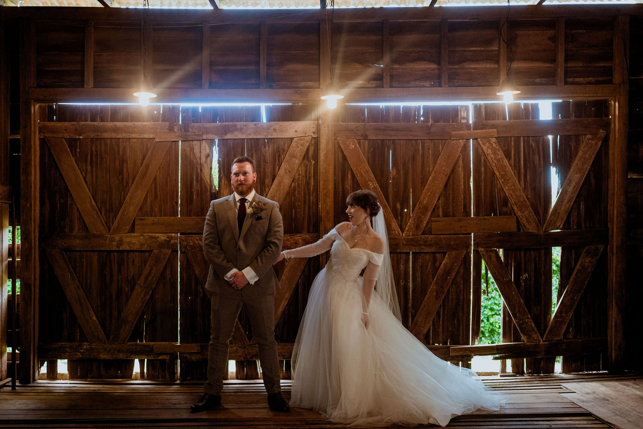 Bride and groom posing together in front of wooden barn doors
