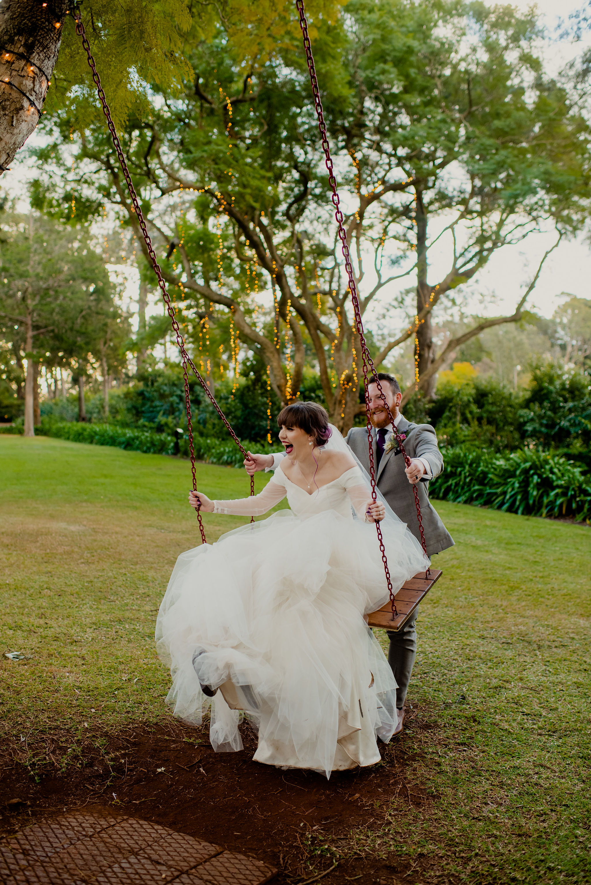 Groom pushes his bride on a swing at Gabbinbar Homestead
