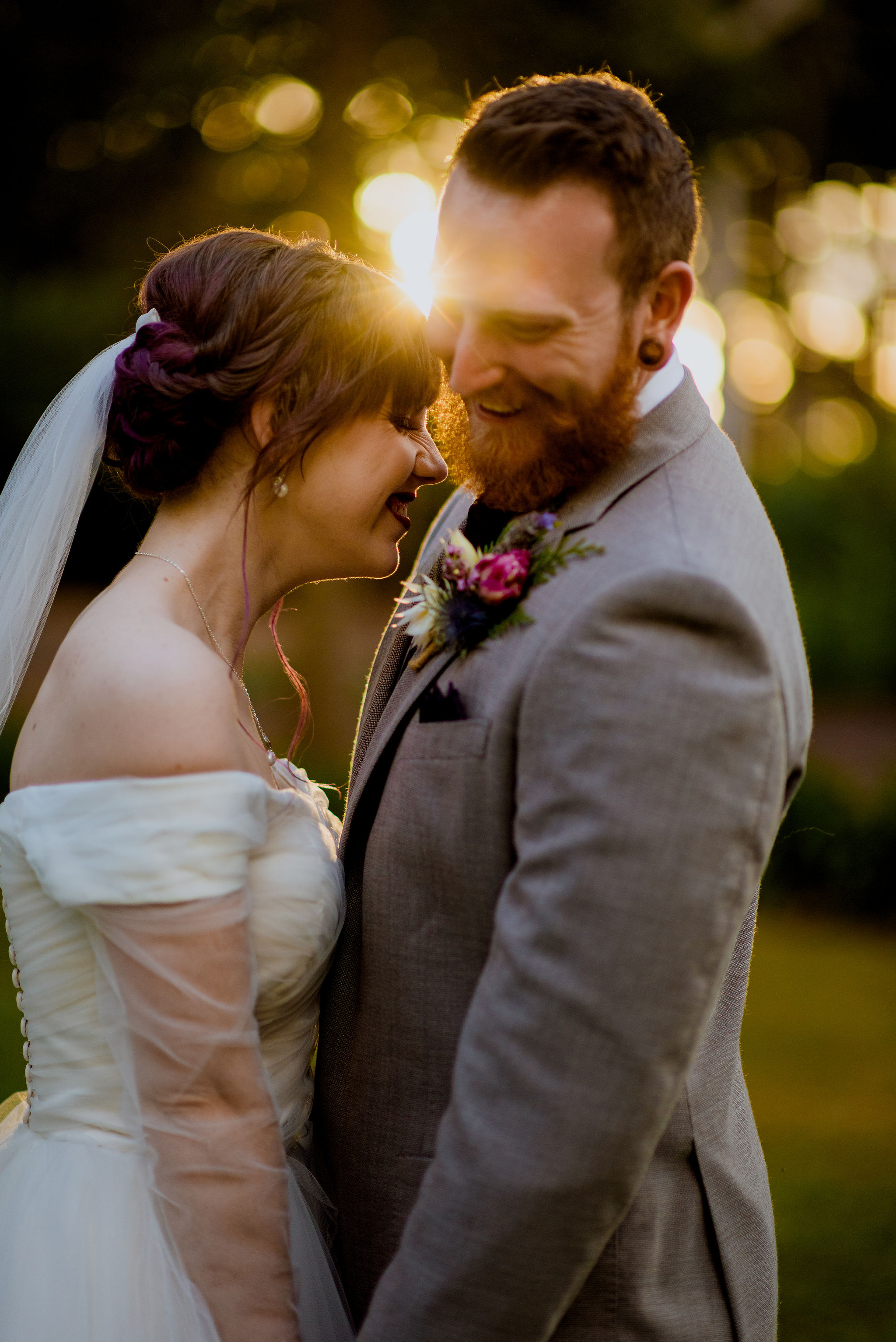 Newlywed bride and groom laugh together with sunset behind them