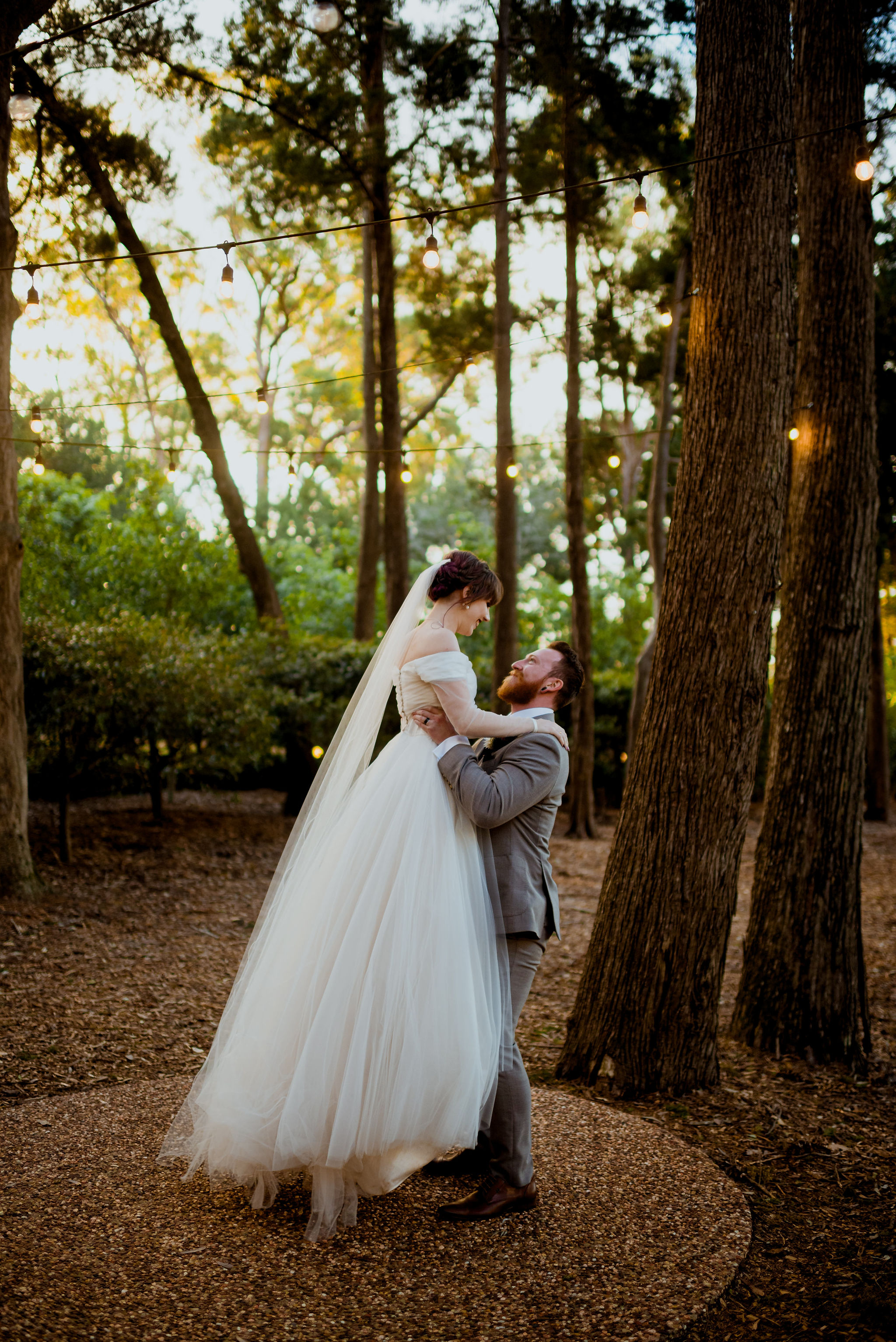 Groom lifts his bride up in a forest