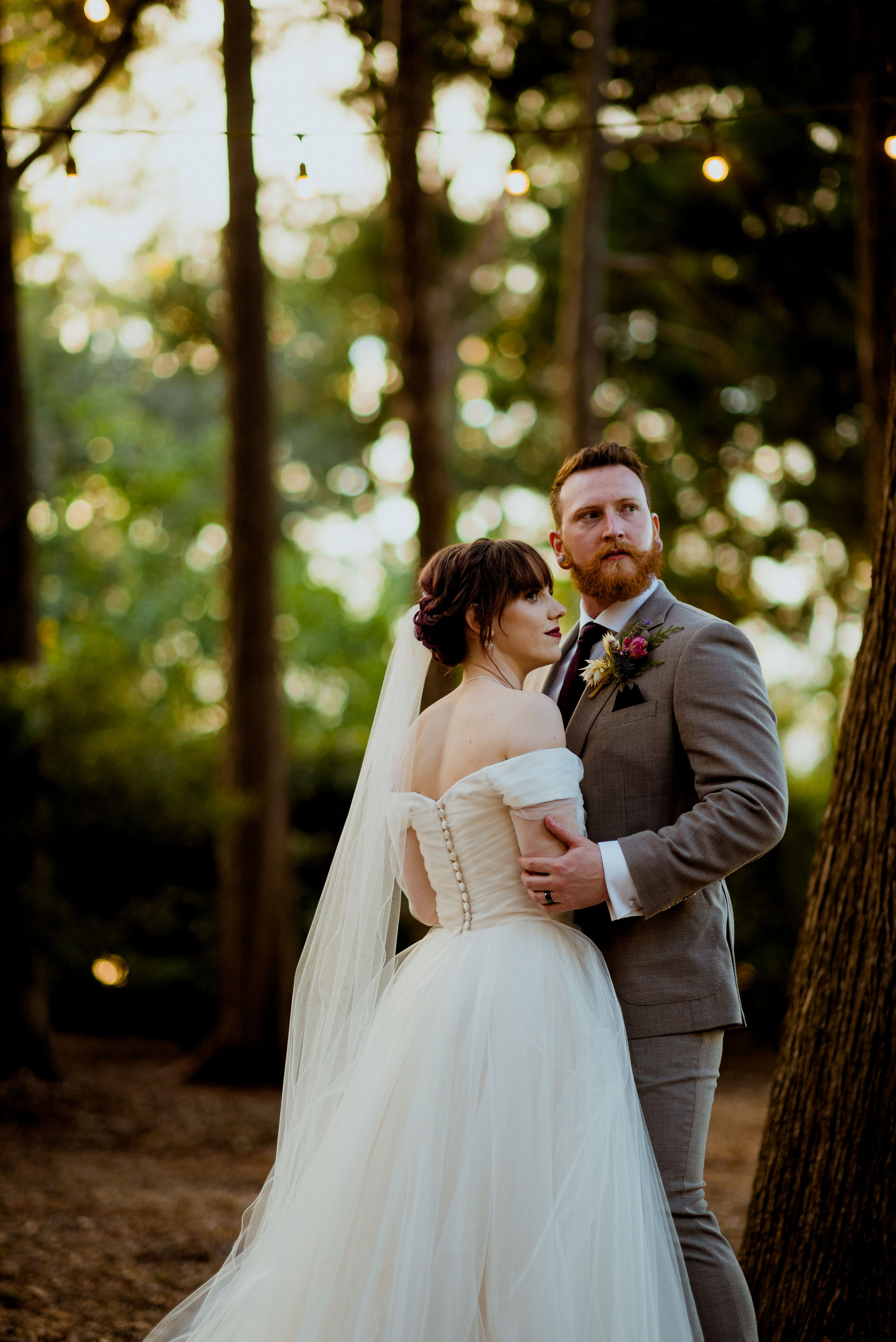 Bride and groom look off into the distance in a forest