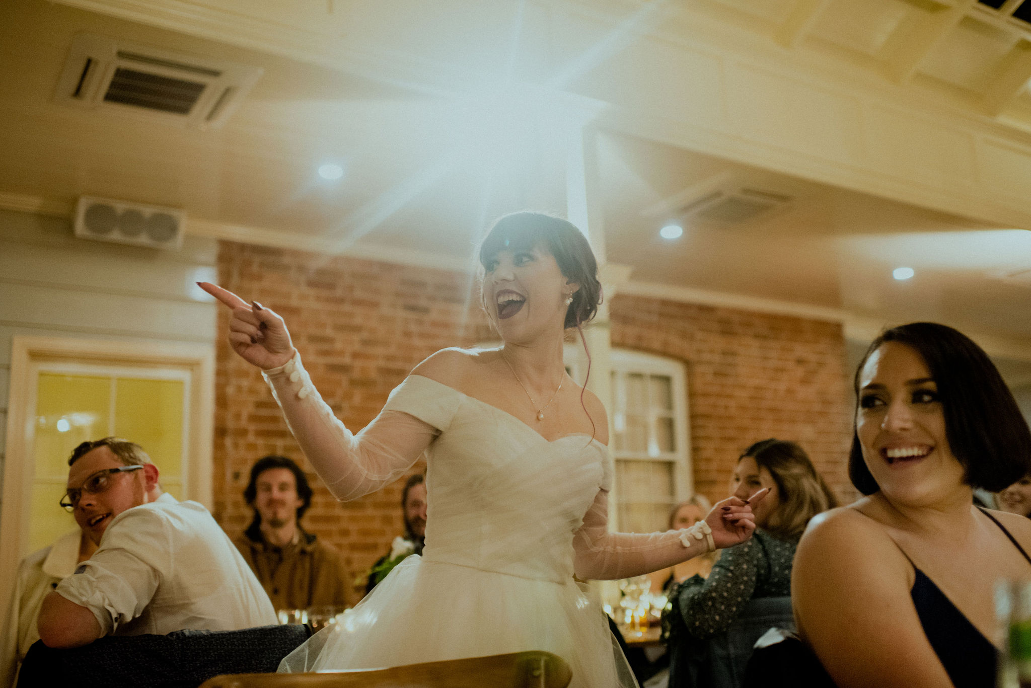 Bride points and laughs with a spotlight behind her