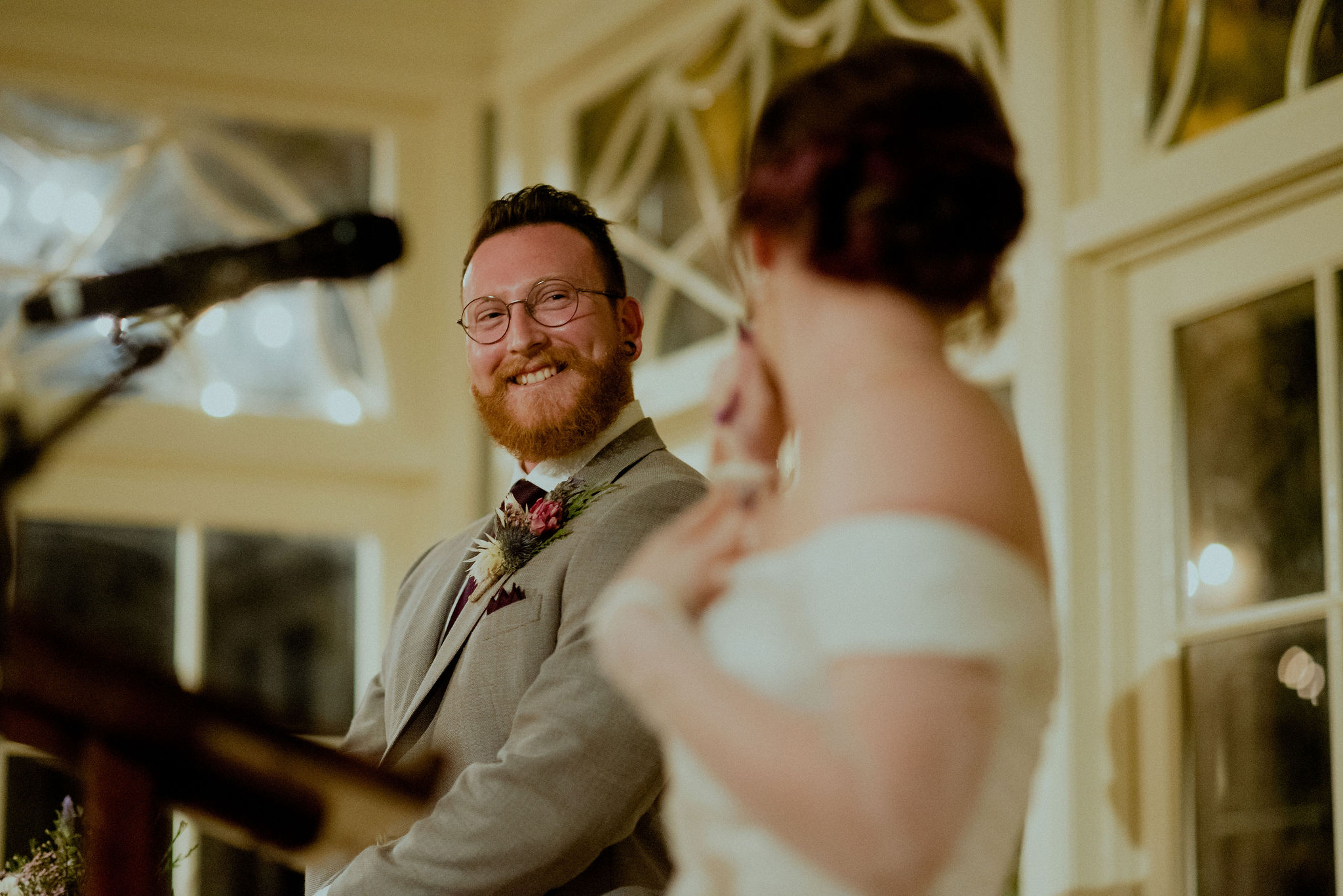 Groom smiles at bride during reception speech
