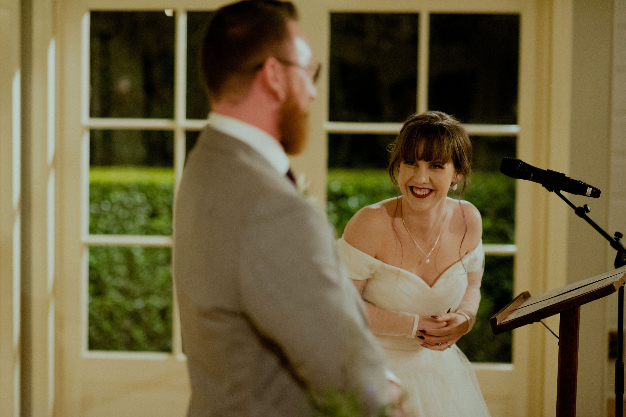 Bride laughs at groom during reception speech