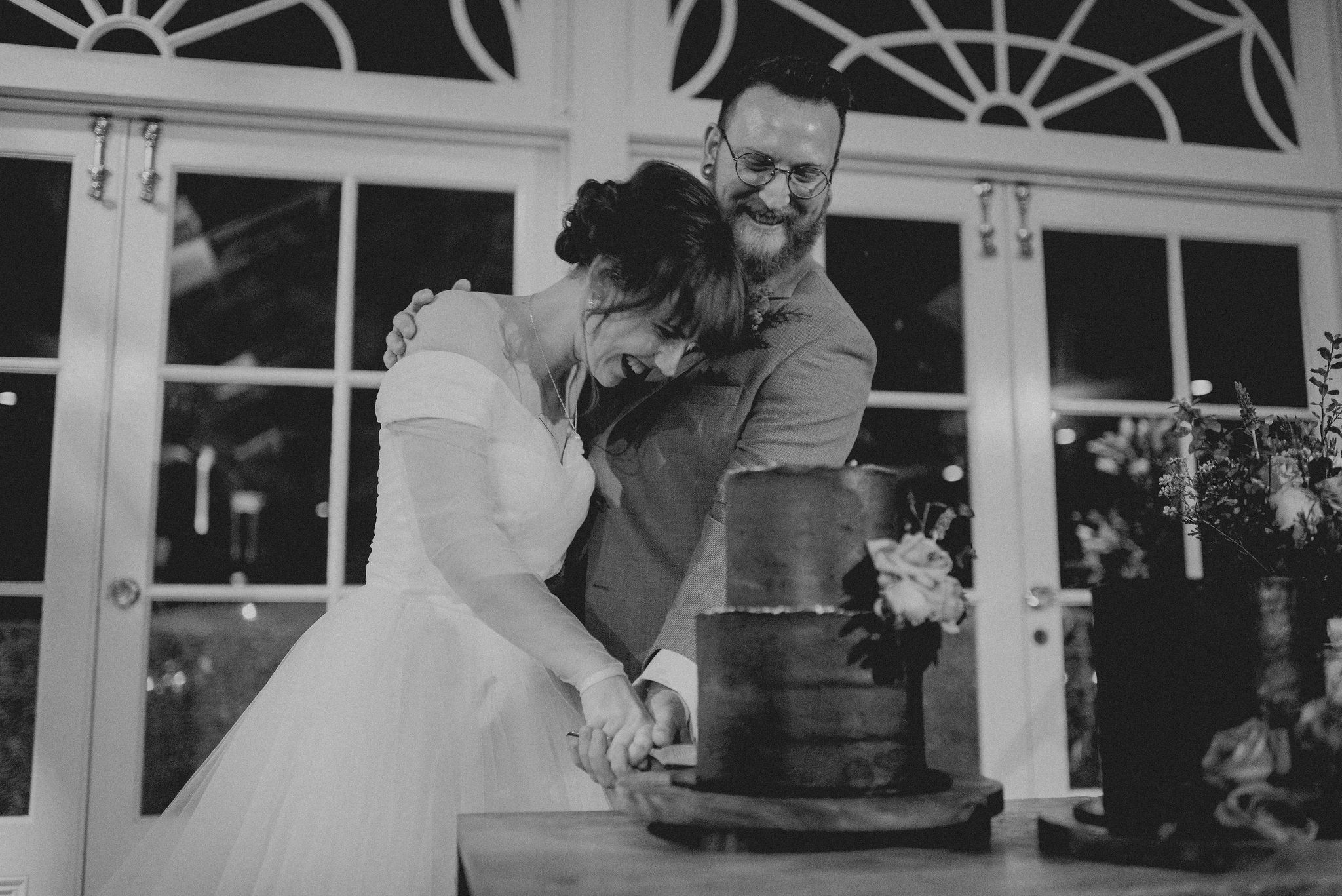 Bride and groom laugh as they cut wedding cake together